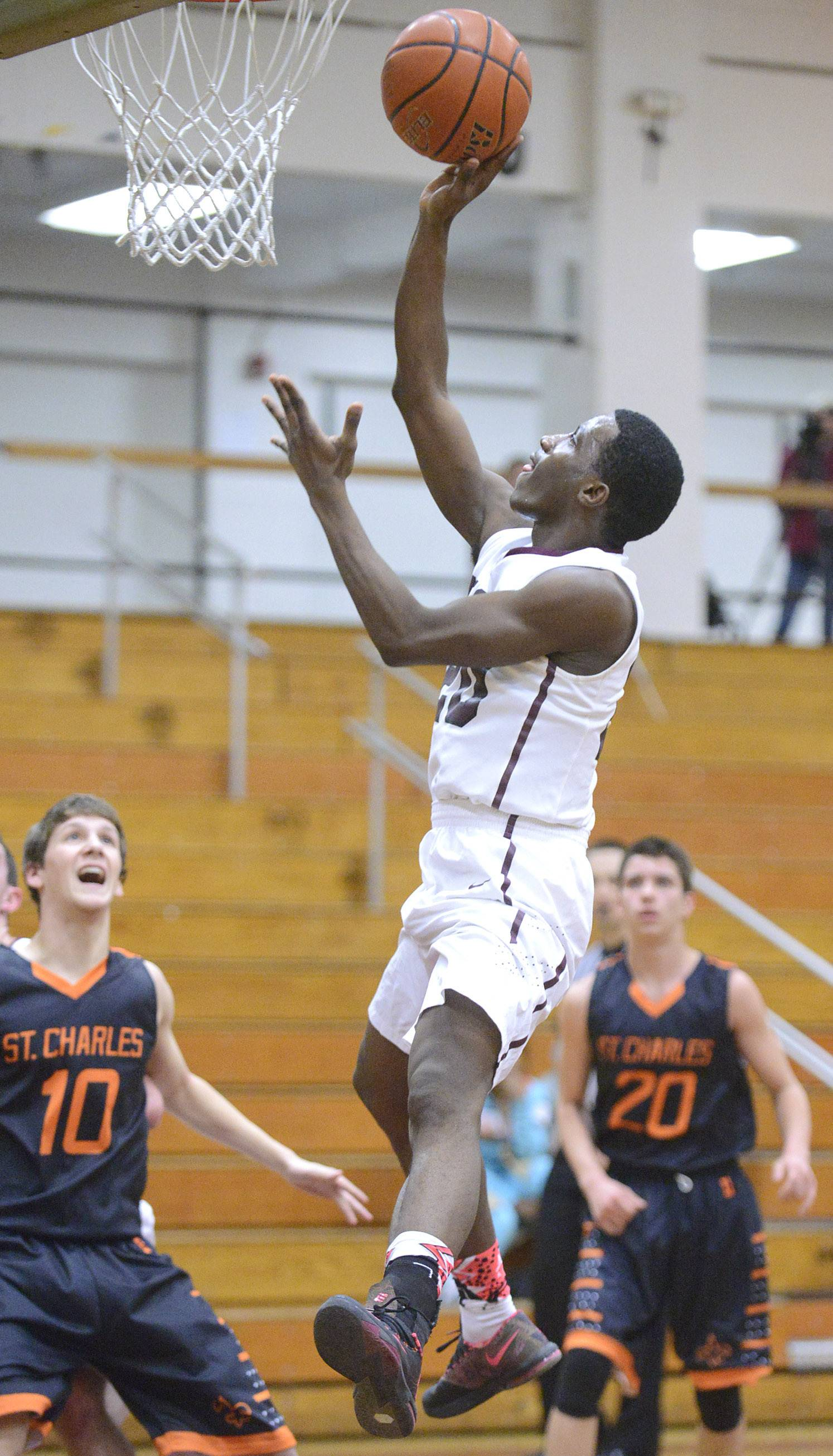 Elgin's Isaiah Butler soars to sink a basket over St. Charles East in the second quarter on Friday.