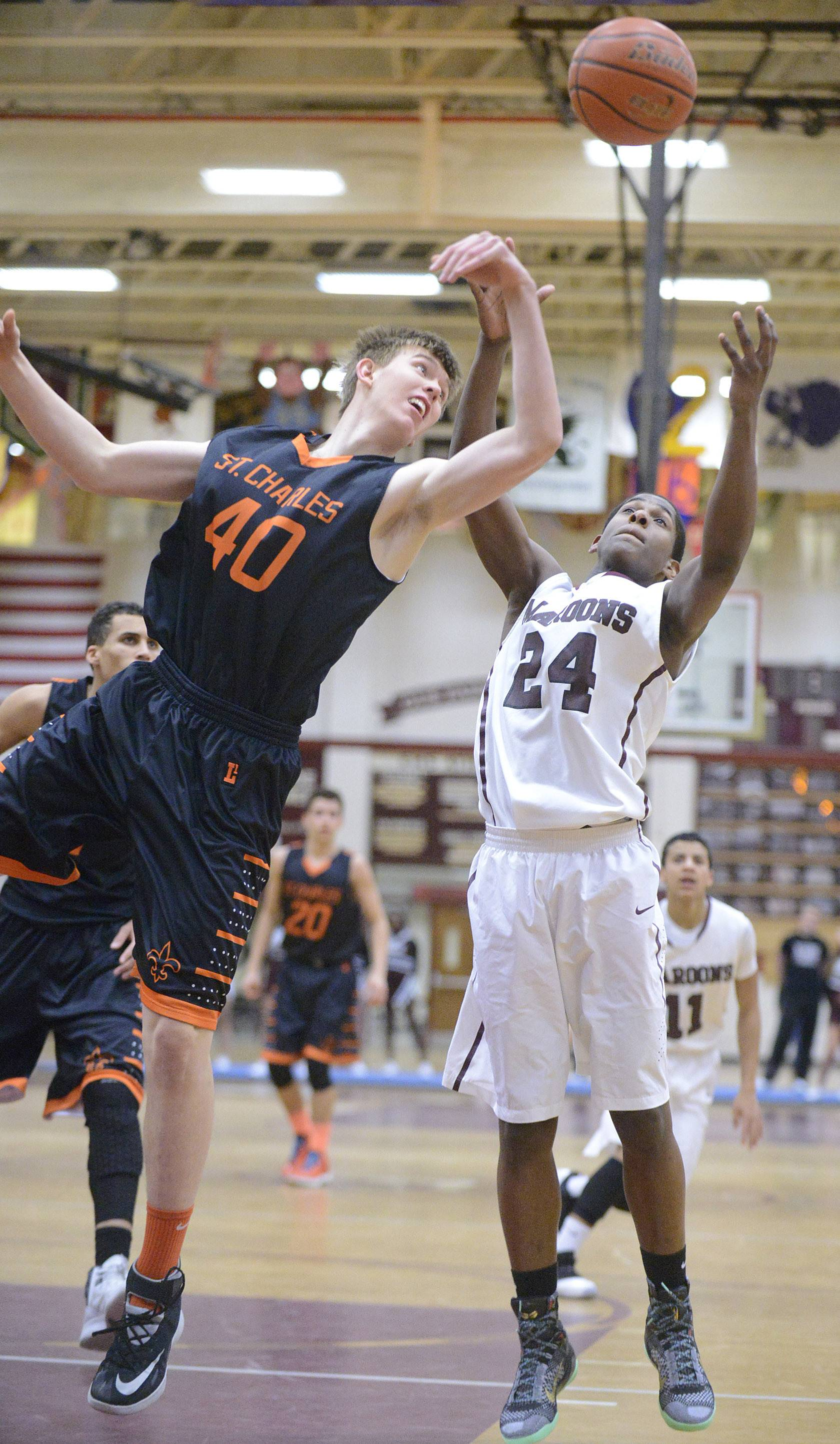 St. Charles East's Jack Bronec and Elgin's Lavion Baldwin leap for a Saints rebound in the third quarter.