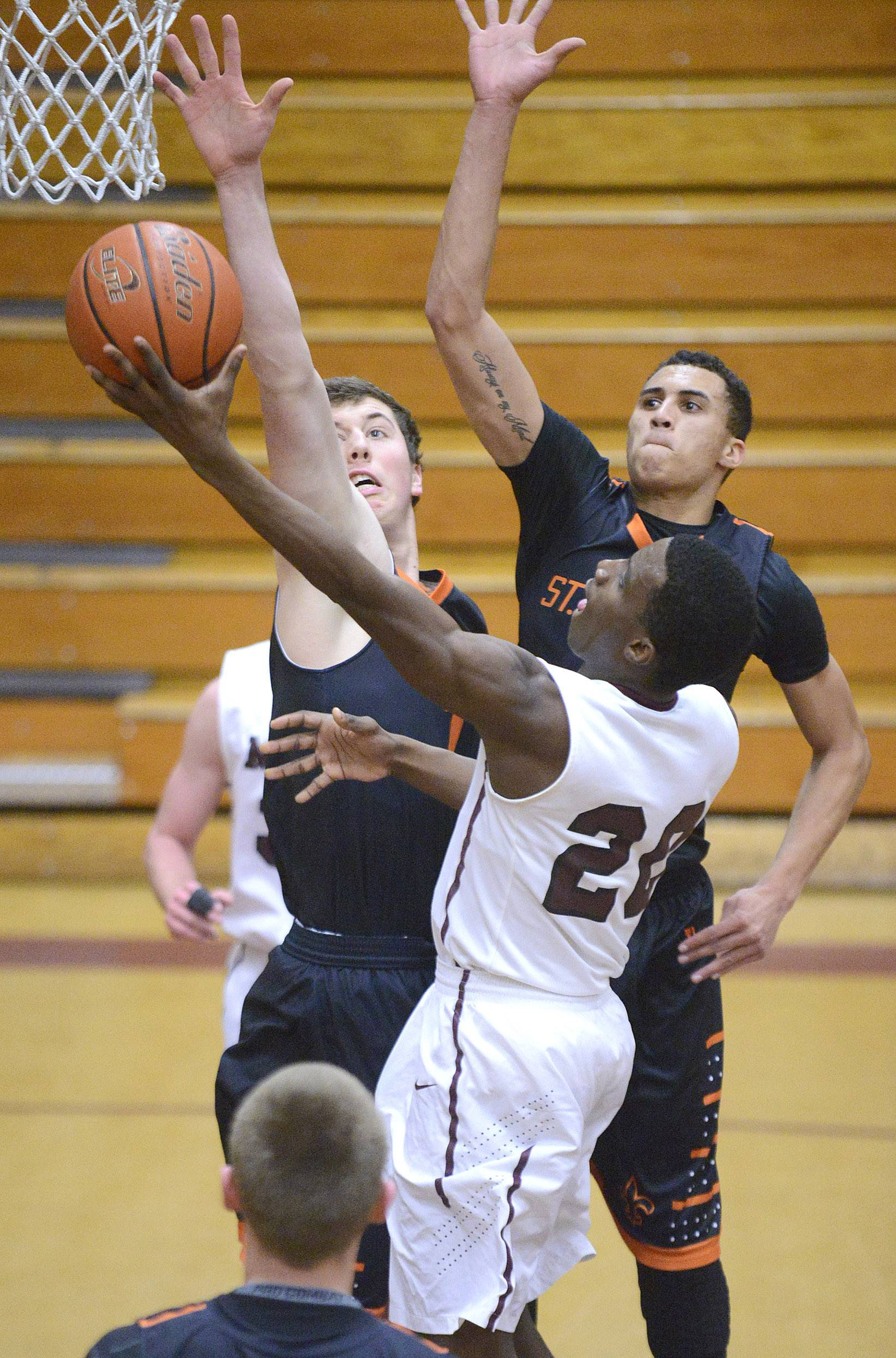 Elgin's Isaiah Butler sinks a shot past St. Charles East's Dave Mason, left, and AJ Washington in the first quarter.