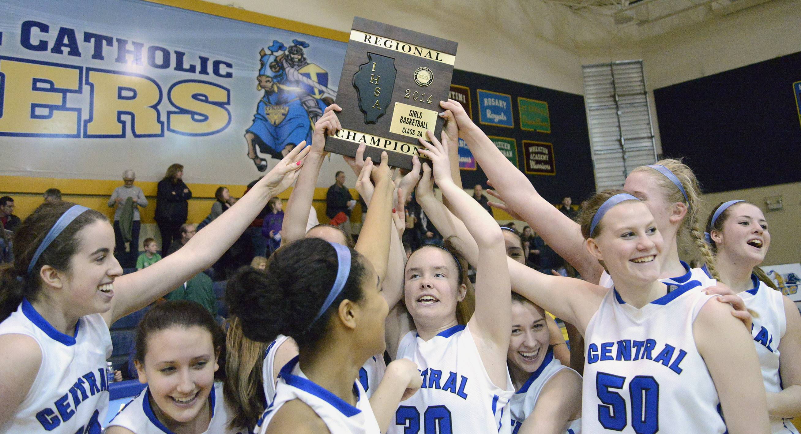 Burlington Central's girls basketball team hoists the Class 3A regional championship plaque after its win over St. Edward on Saturday in Aurora. Cassandra Ciganek (30) helps hold up the plaque from the center.