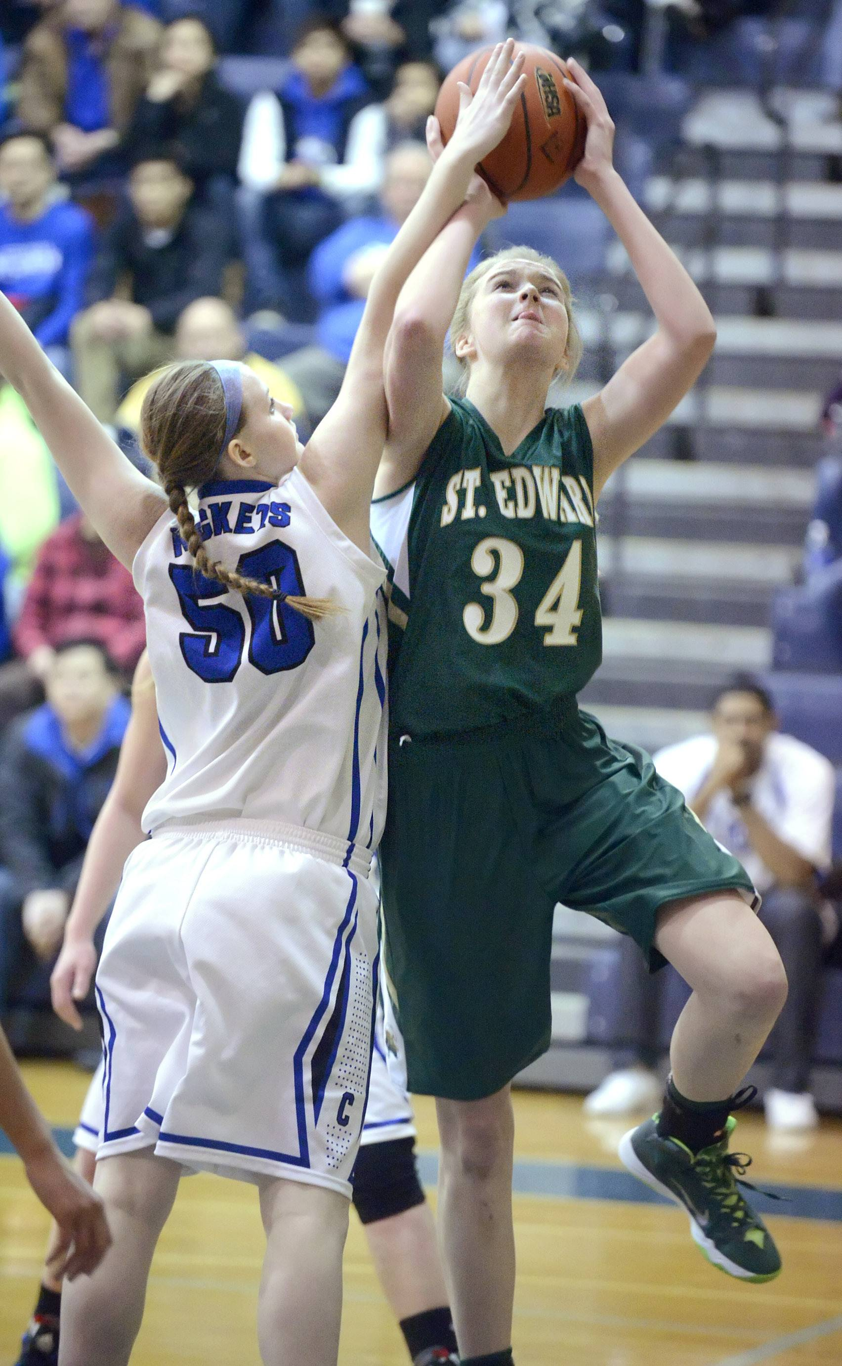Burlington Central's Rebecca Gerke attempts to block a shot by St. Edward's Cicile Rapp in the first quarter of the Class 3A regional championship game on Saturday, February 22.