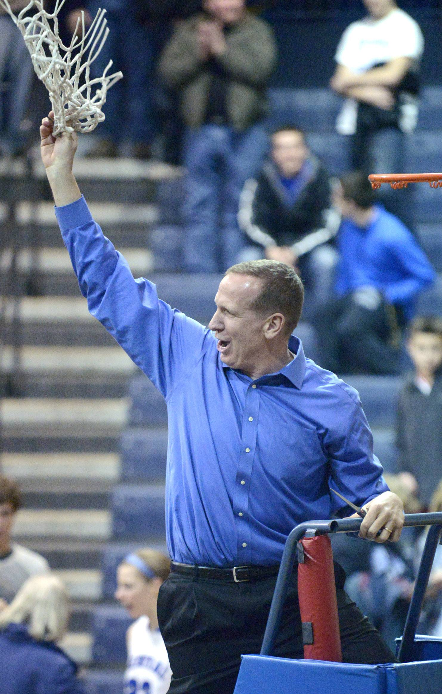 Burlington Central head coach Mark Smith twirls the hoop in the air before tossing it to his team after their victory over St. Edward in the Class 3A regional championship game on Saturday, February 22.