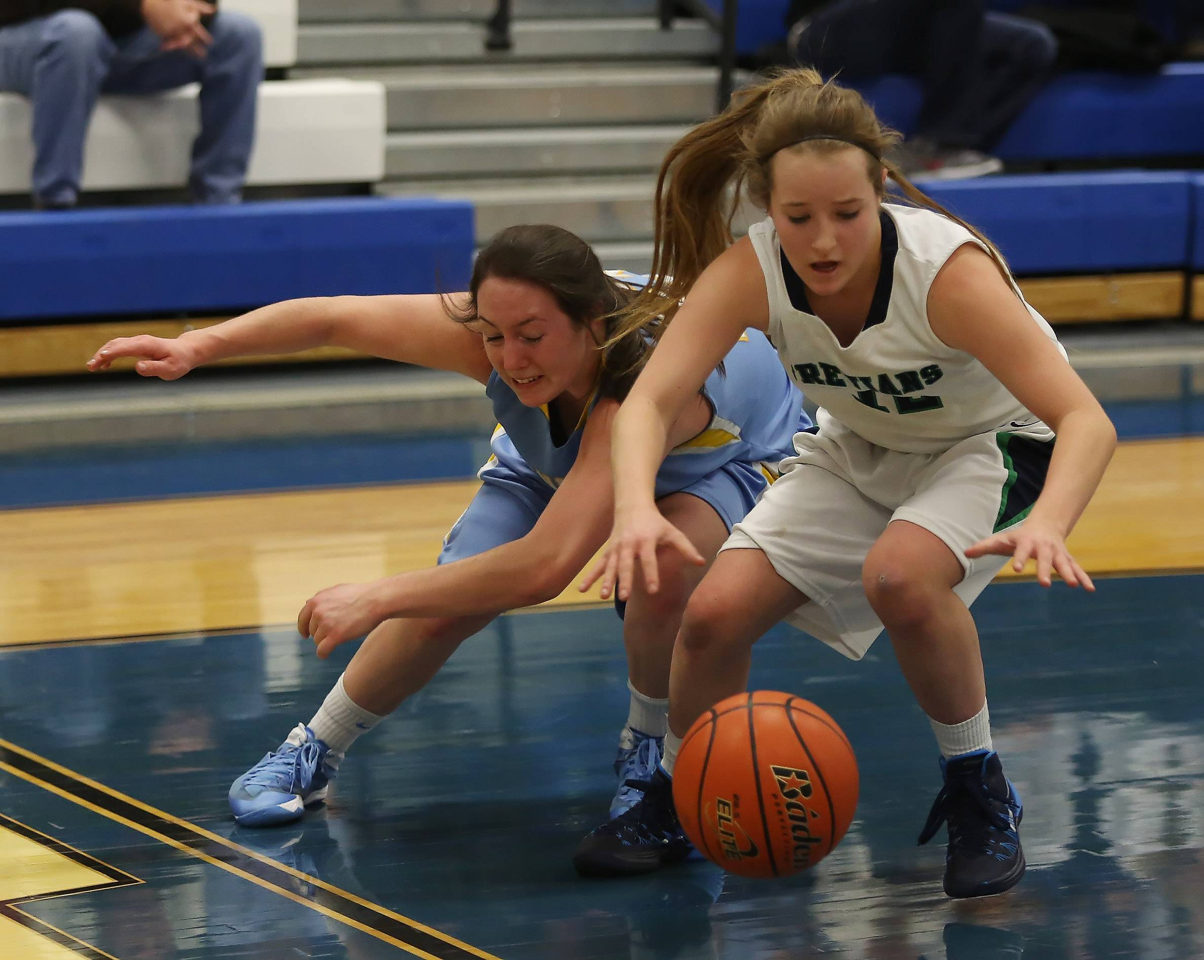 Maine West guard Abbey Herling, left, battles New Trier guard Megan Neuhaus for a loose ball during Monday's Class 4A sectional semifinal at Maine East.
