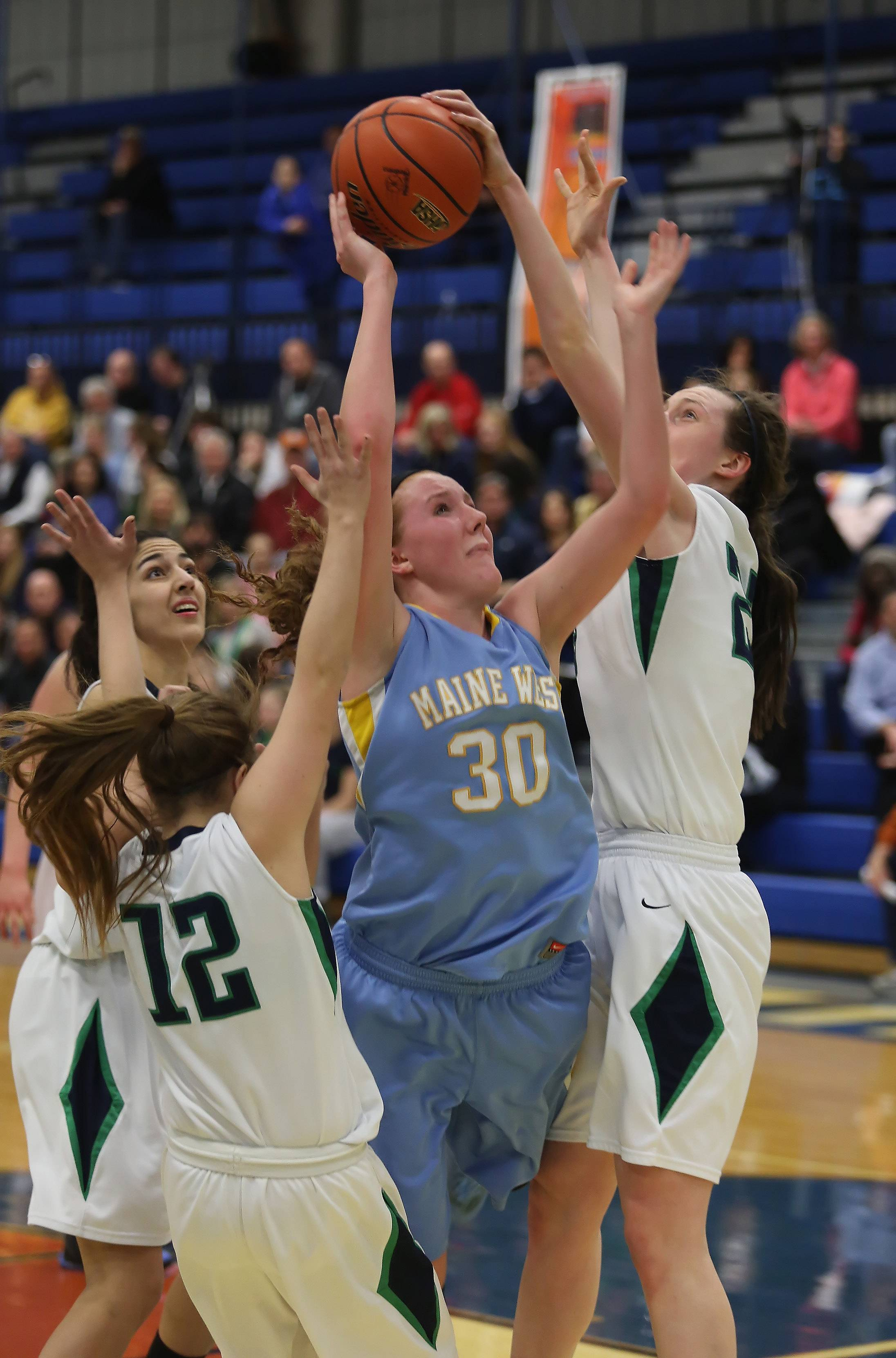Maine West forward Brittany Collins is fouled by New Trier defenders Megan Neuhaus, left, and Jeanne Boehm during Monday's Class 4A sectional semifinal at Maine East.
