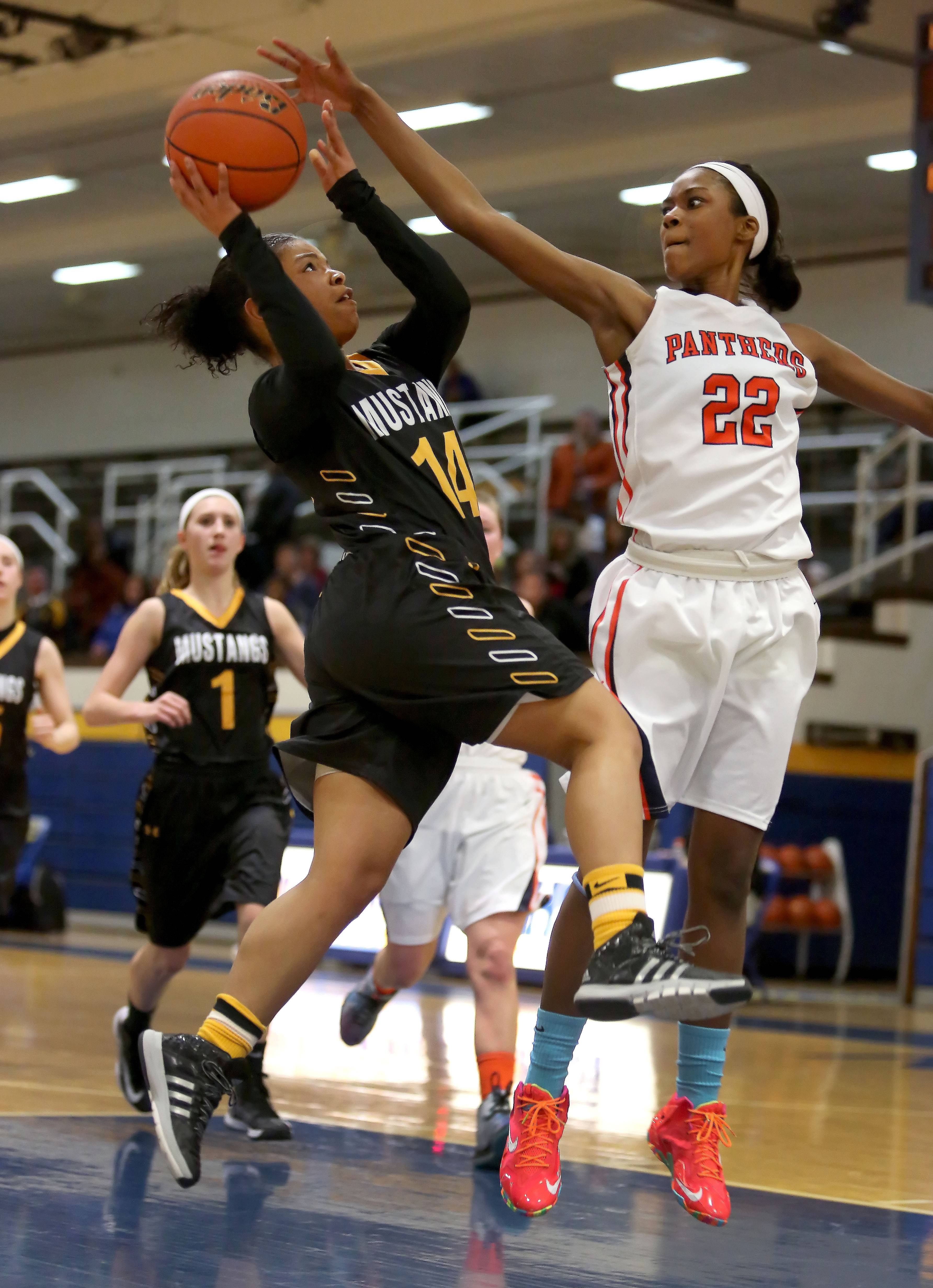 Metea Valley's Kellee Clay, left, makes her way to the basket as Amri Wilder of Oswego stops her.