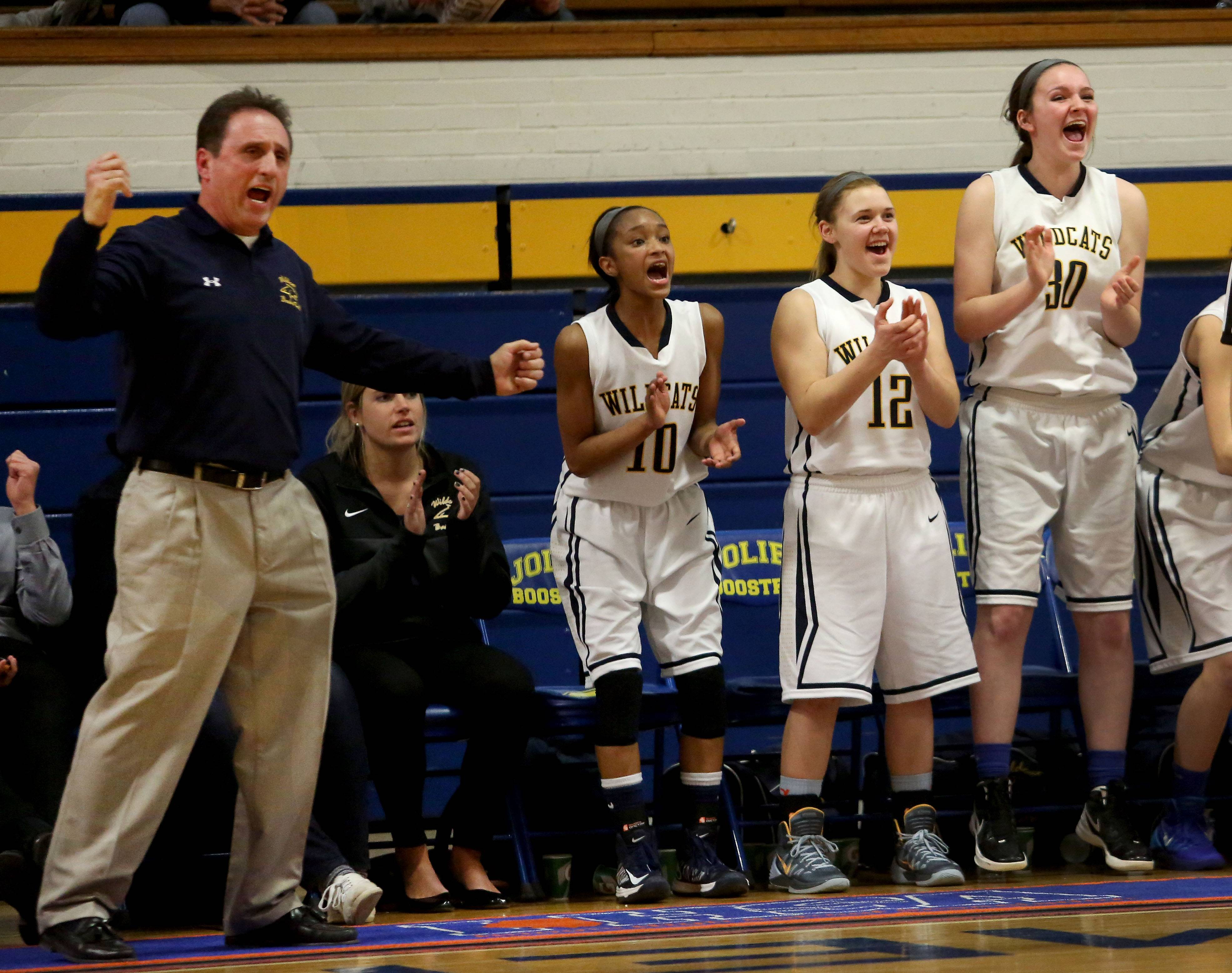 Neuqua Valley head coach Mike Williams and players on the bench cheer in their win over Benet Academy.