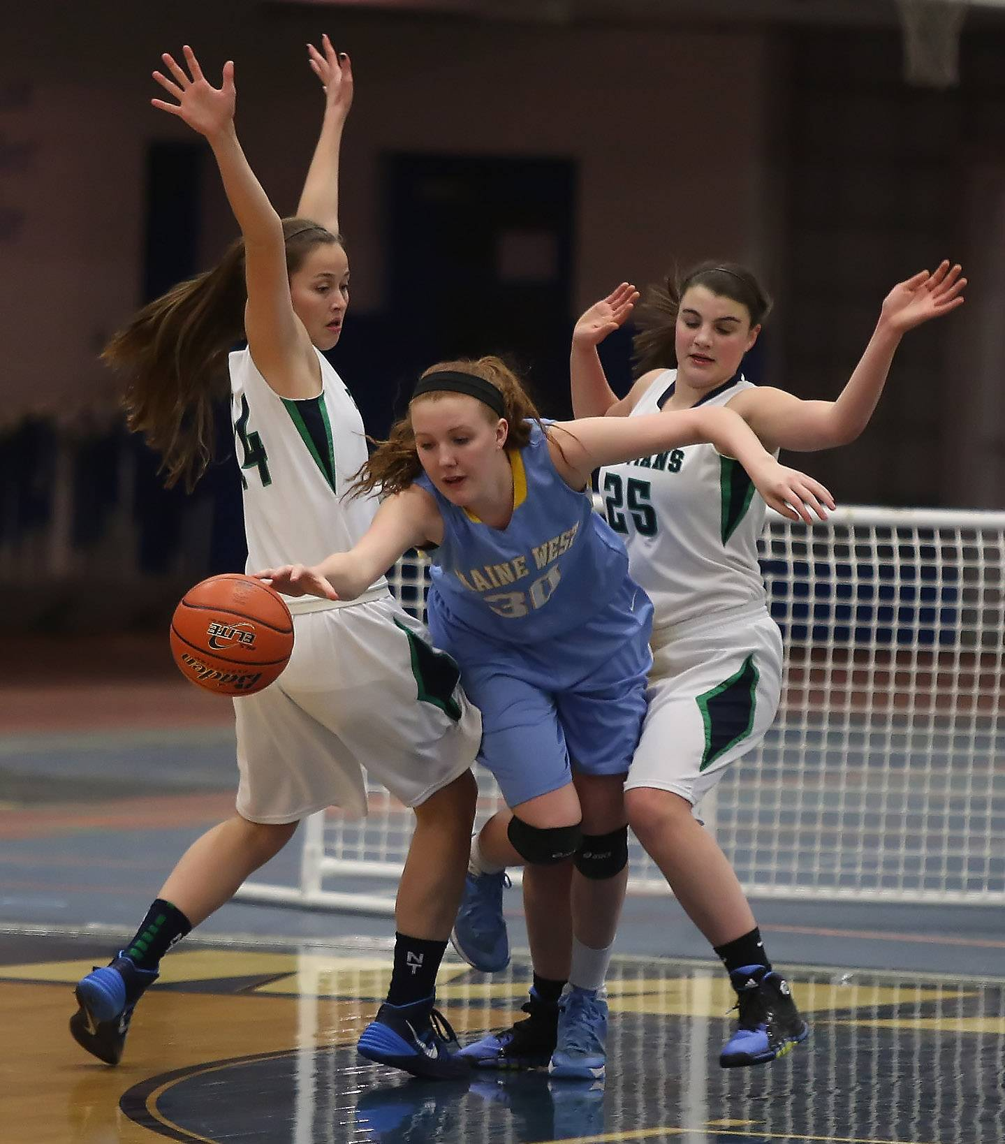 Maine West forward Brittany Collins splits between New Trier defenders Jackie Welch, left, and Kathryn Pedi.