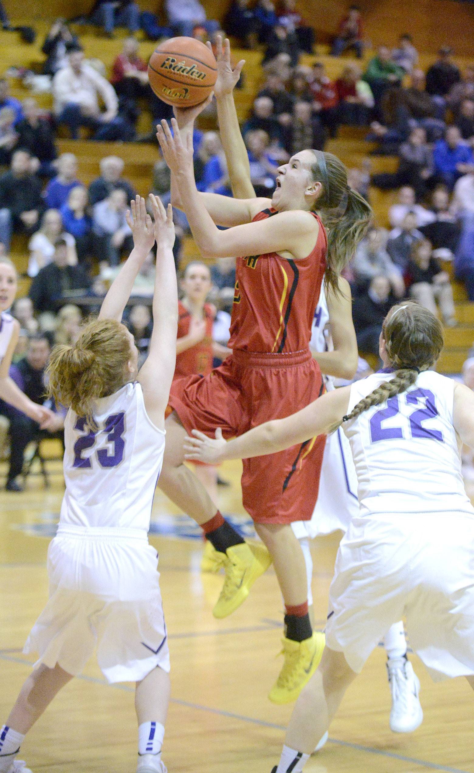 Batavia's Liza Fruendt shots over a block by Downers Grove North's Lauren Porcelli, left, and Colleen Horn in the second quarter of the 4A sectional semifinals at Addison Trail High School in Addison on Tuesday, February 25.
