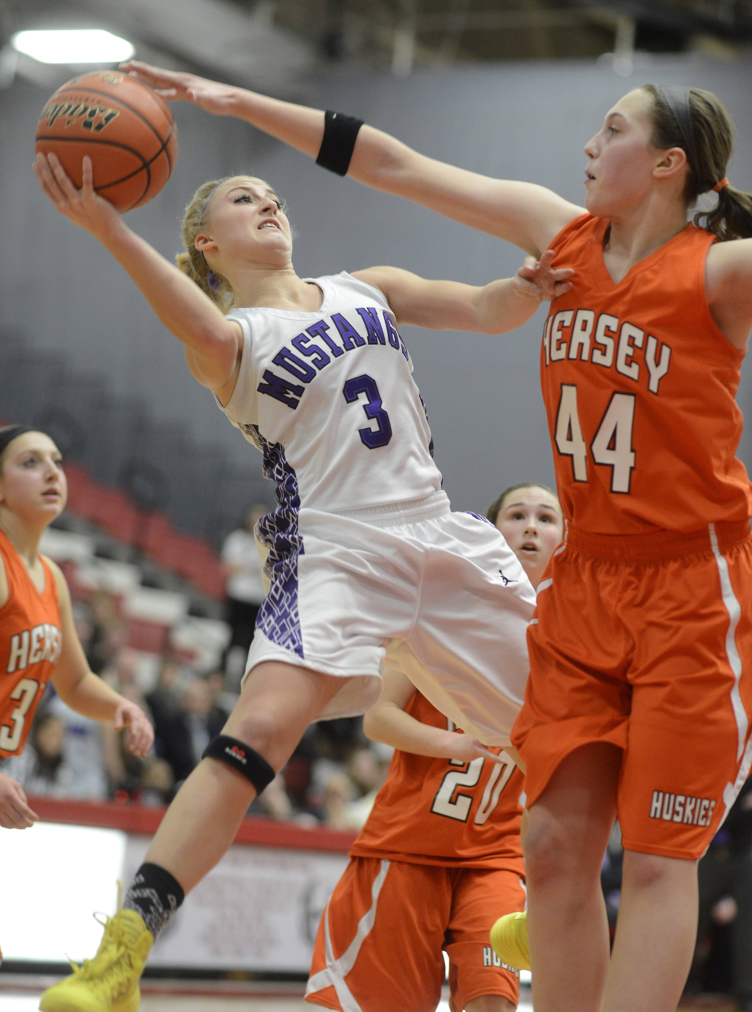 Rolling Meadows' Jackie Kemph, left, has her shot blocked on a drive to the basket by Hersey's Maggie Berigan during the Barrington sectional semifinals Tuesday.