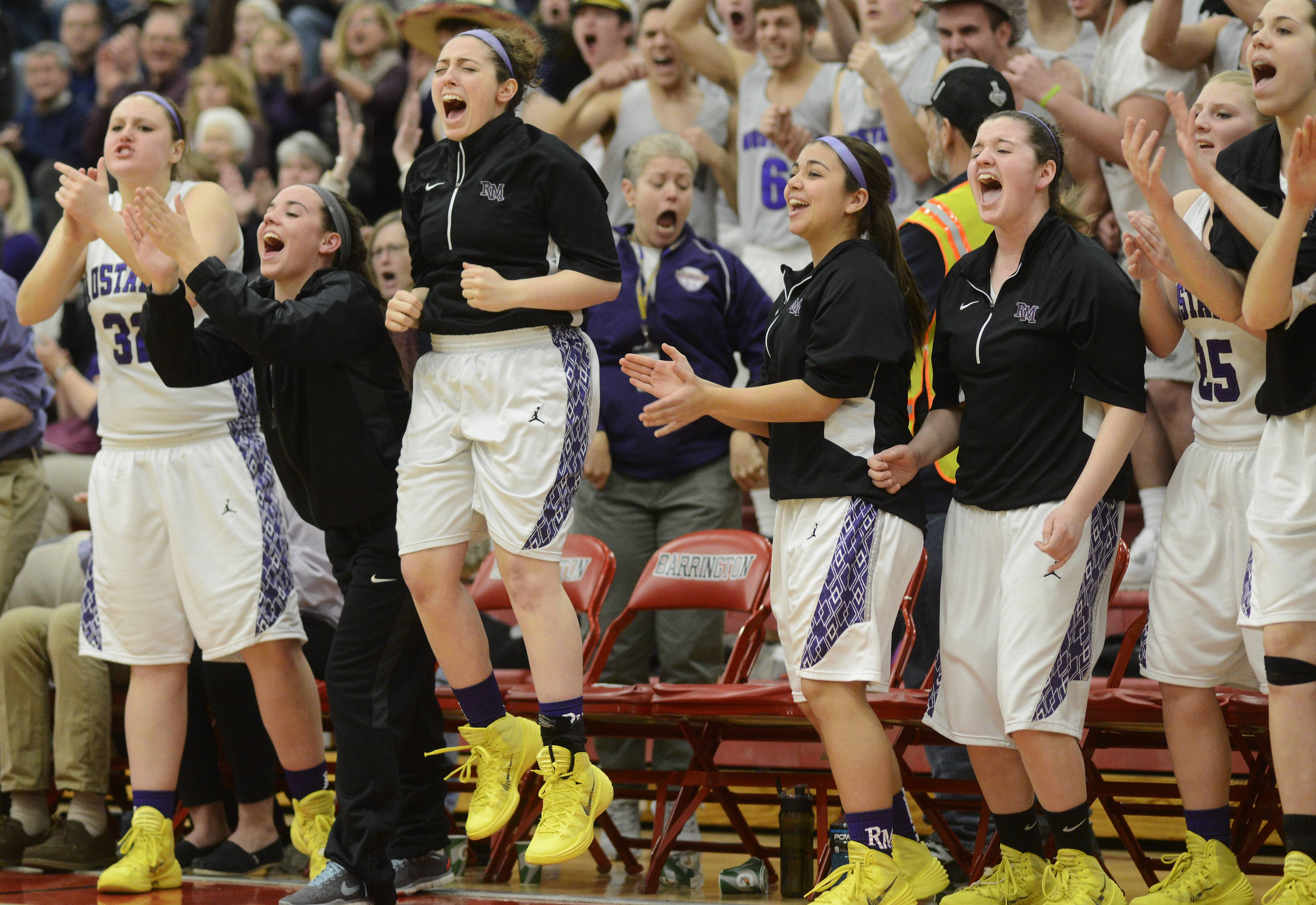 Players on the Rolling Meadows bench celebrate as their team takes a fourth-quarter lead .
