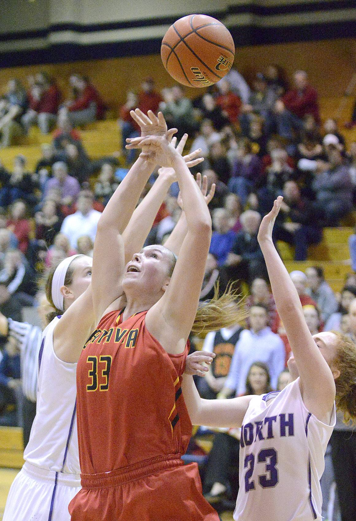 Downers Grove North's Peyton Winters, left, and Lauren Porcelli, right, leap for a rebound with Batavia's Erin Bayram in the fourth quarter .