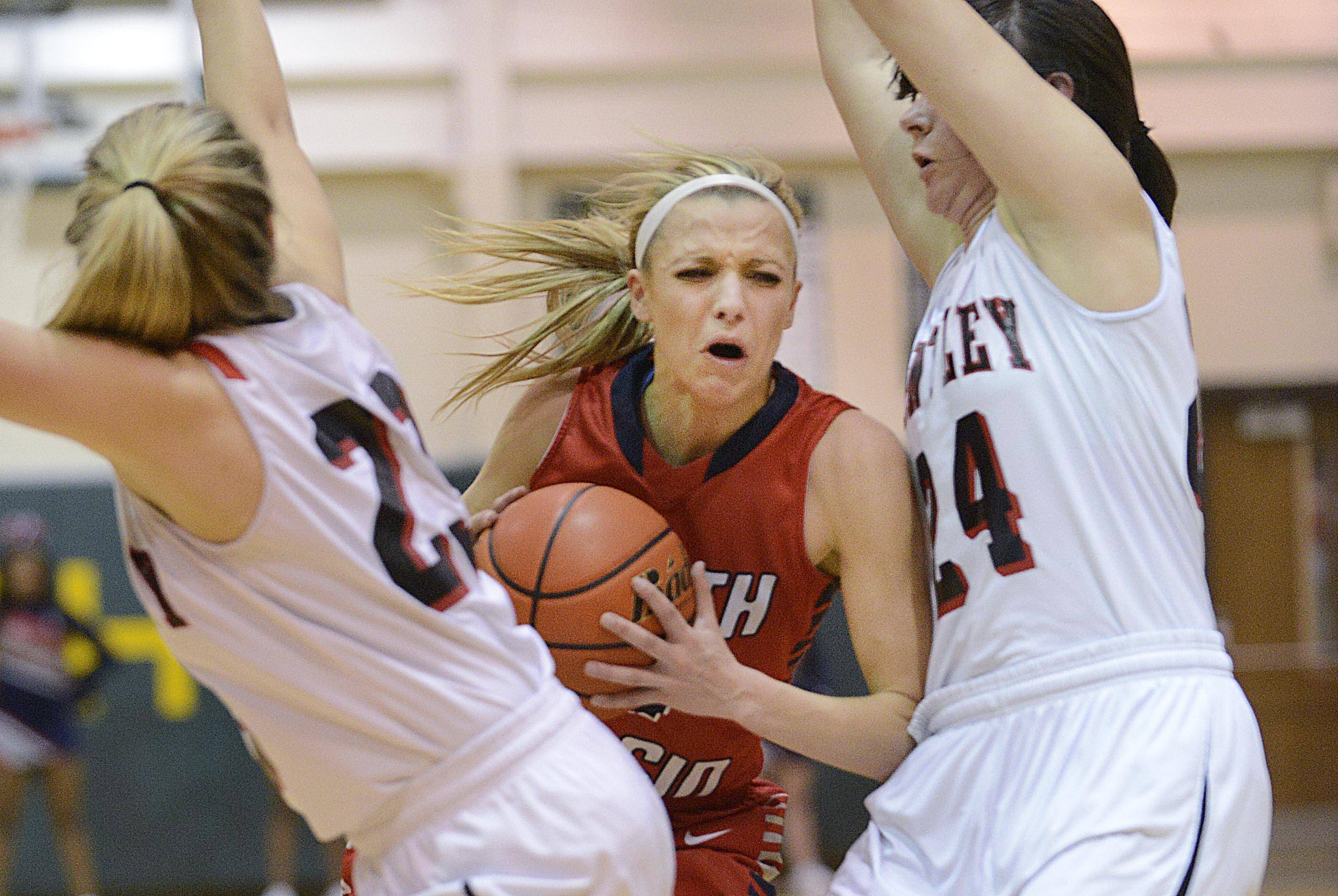 South Elgin's Savanah Uveges pushes through the defense of Huntley's Bethany Zornow and Jessica Brock in the Class 4A Crystal Lake South sectional game Tuesday.