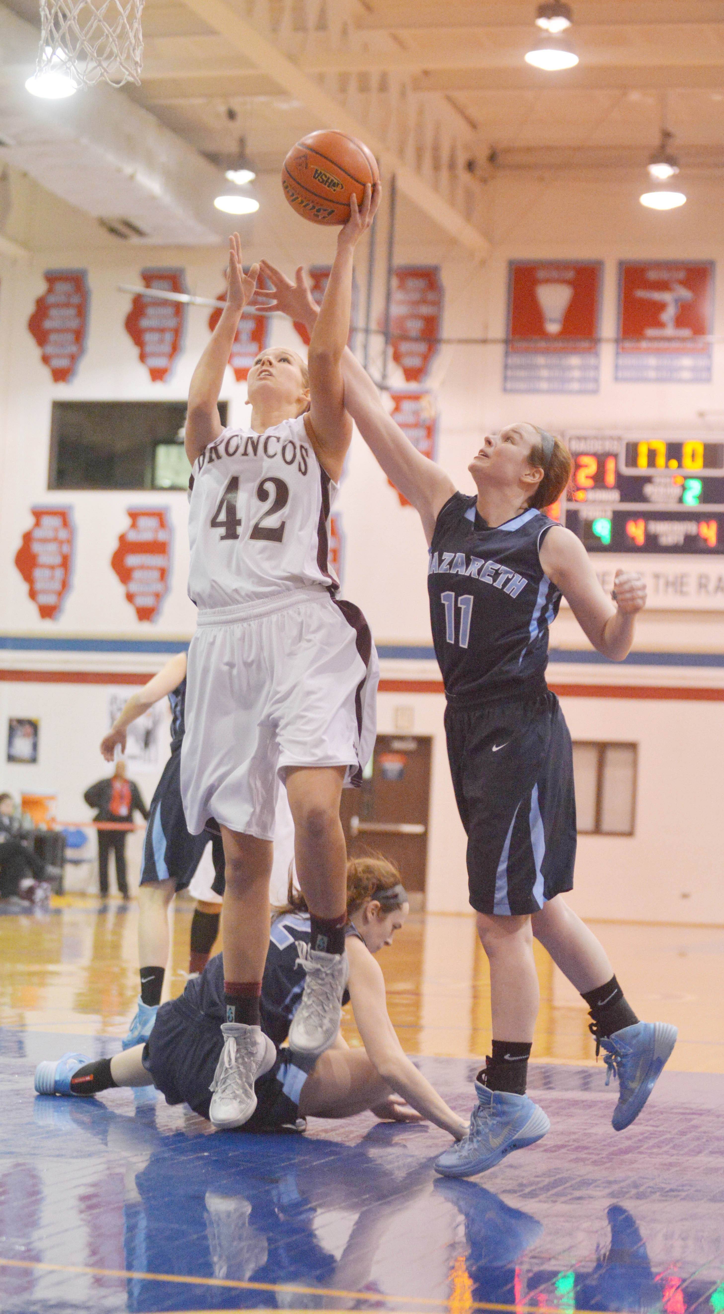 Claire Jakaitis of Montini takes a shot as Mary Clare Harrington of Nazareth blocks.