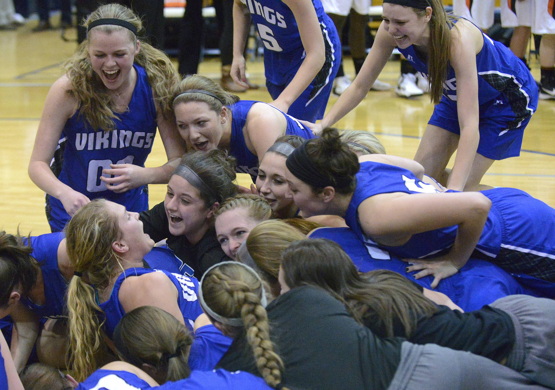 Geneva's Janie McCloughan, center bottom left, is tacked by her teammates after a Vikings win over Wheaton Warrenville South. McCloughan made the winning free throw to bring the team to victory.