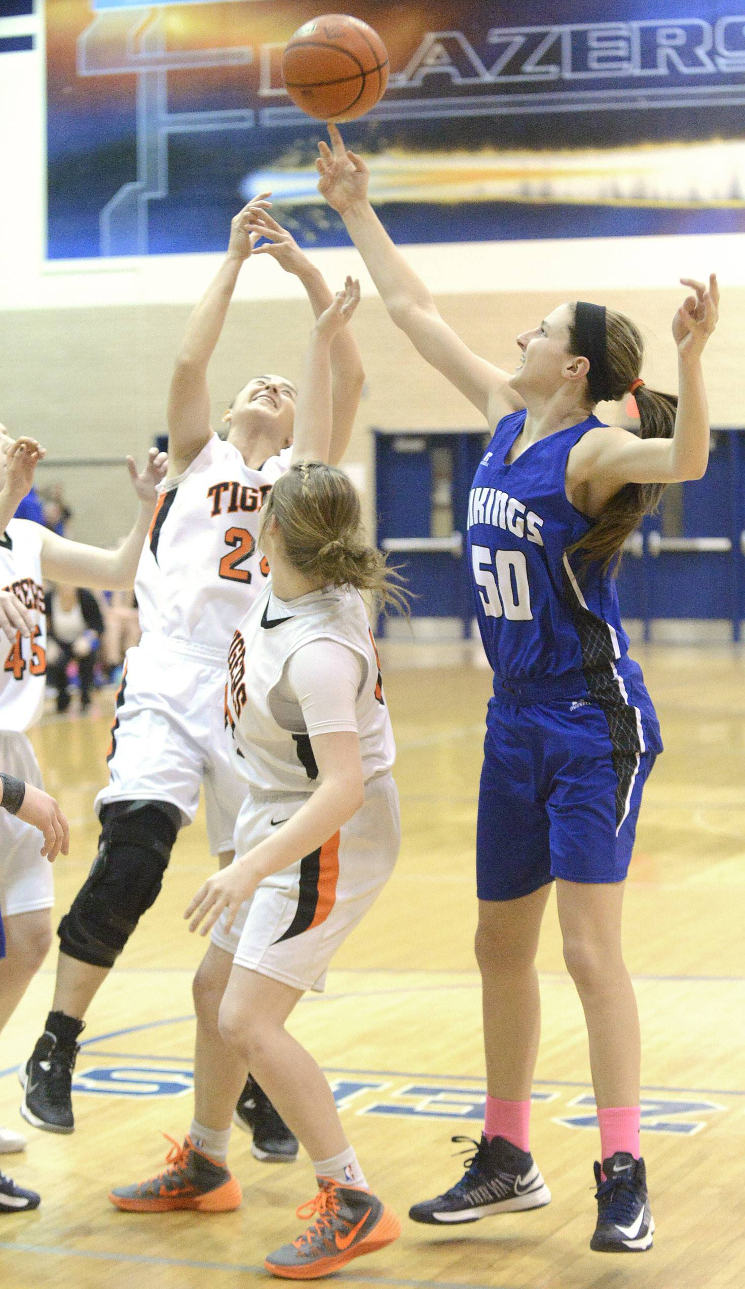 Wheaton Warrenville South's Maggie Dansdill ,left, and Olivia Linebarger attempt to block a shot by Geneva's Grace Loberg in the first quarter.