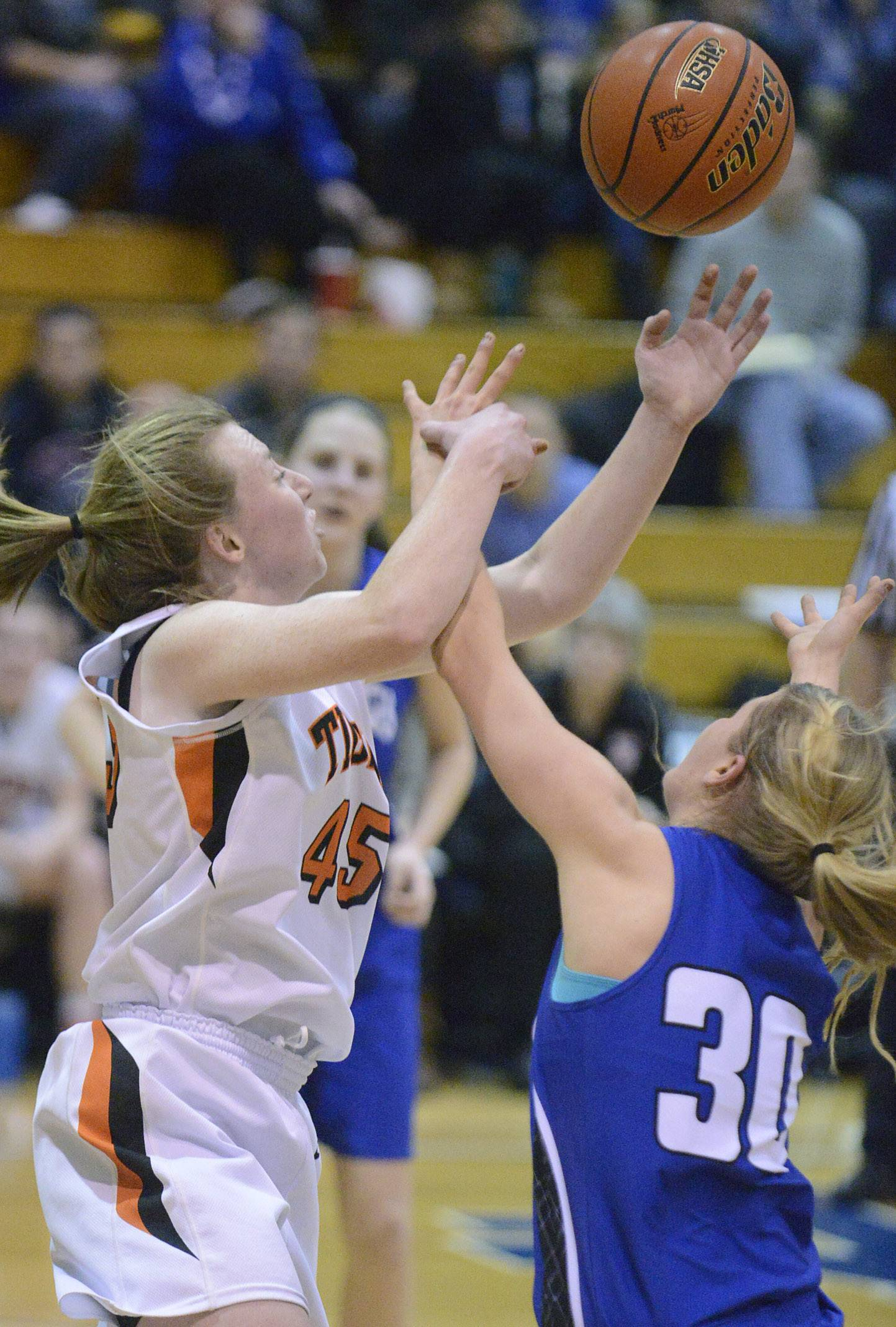 Wheaton Warrenville South's Meghan Waldron and Geneva's Janie McCloughhan fight for a rebound in the second quarter.