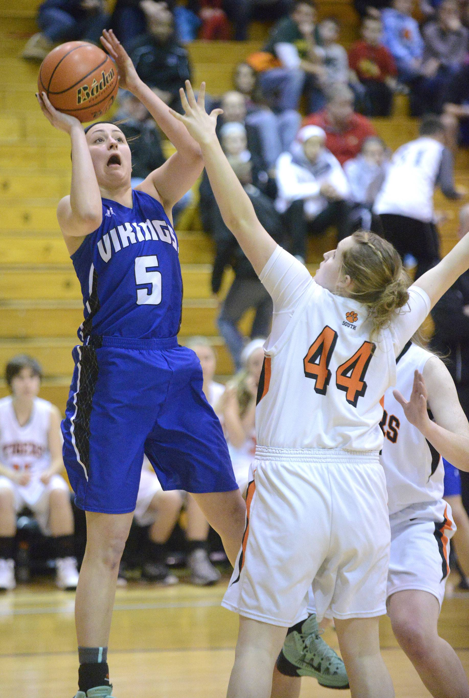 Geneva's Abby Novak shots over a block by Wheaton Warrenville South's Olivia Linebarger  in the second quarter.
