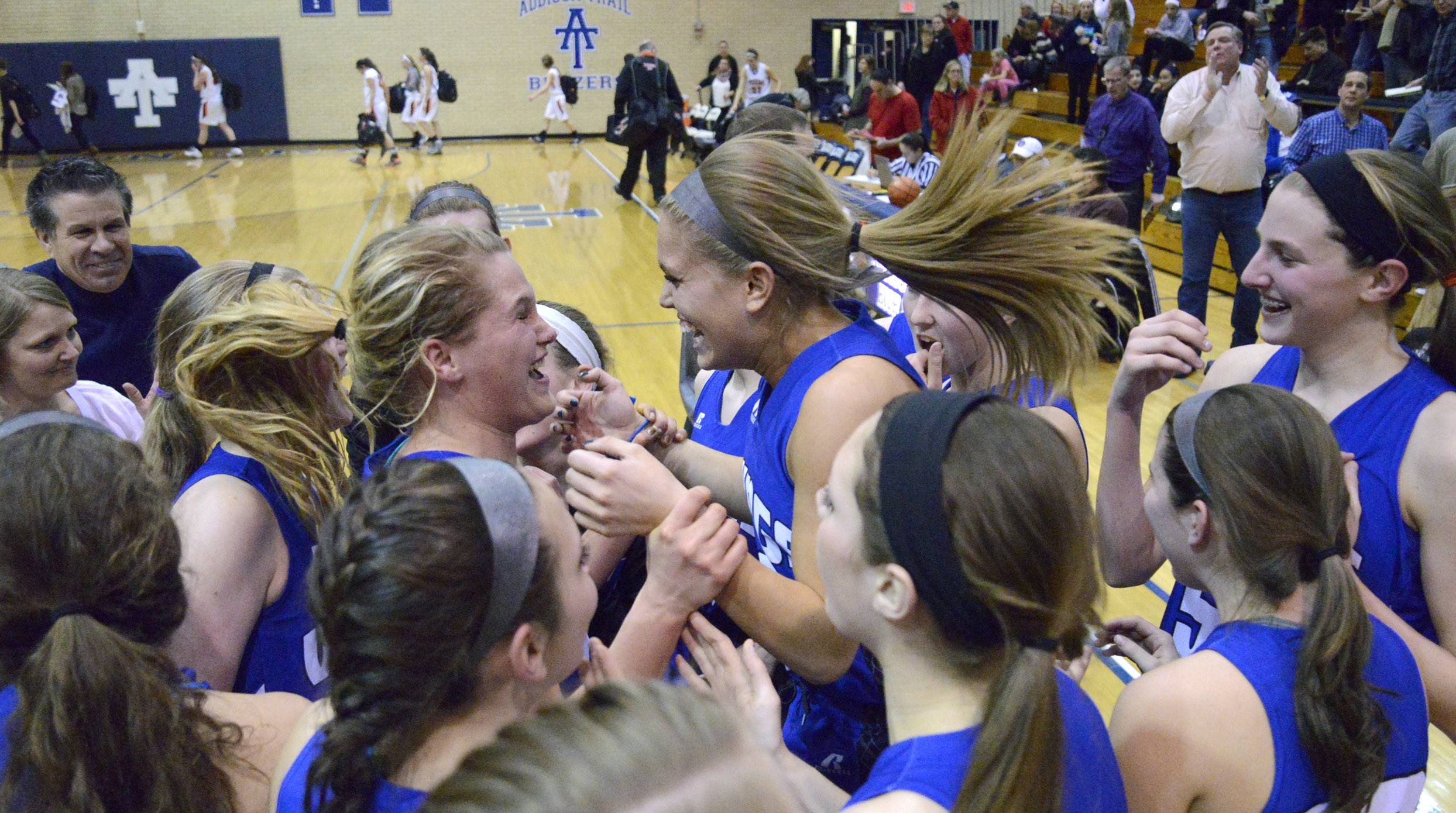 Geneva's Janie McCloughan, center left, celebrates with teammate Bella Medina while surrounded by the Vikings team after McCloughan made the winning free throw .
