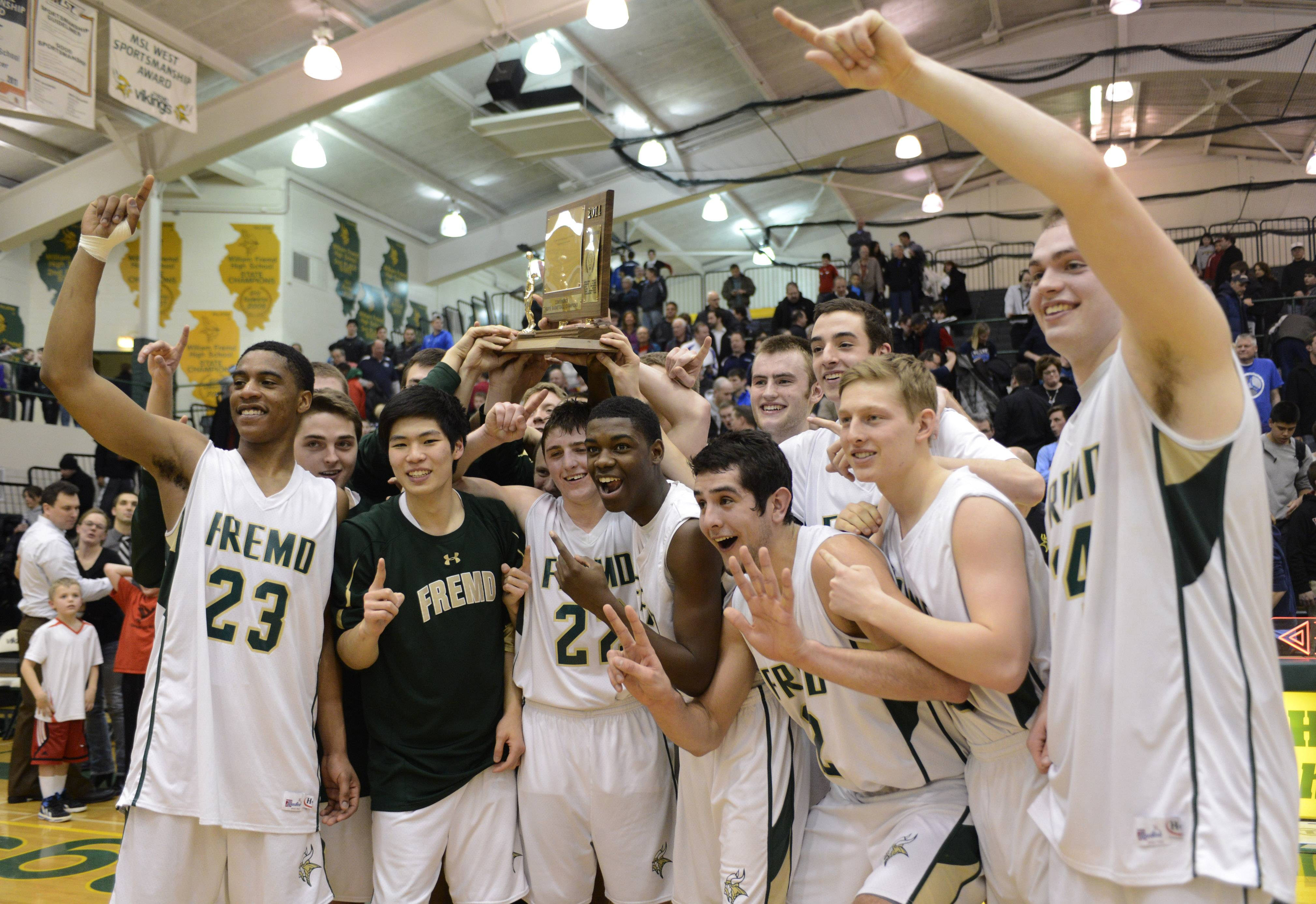 Fremd players hold their Mid-Suburban League championship trophy after defeating Prospect in the title game 55-52 on Wednesday in Palatine.