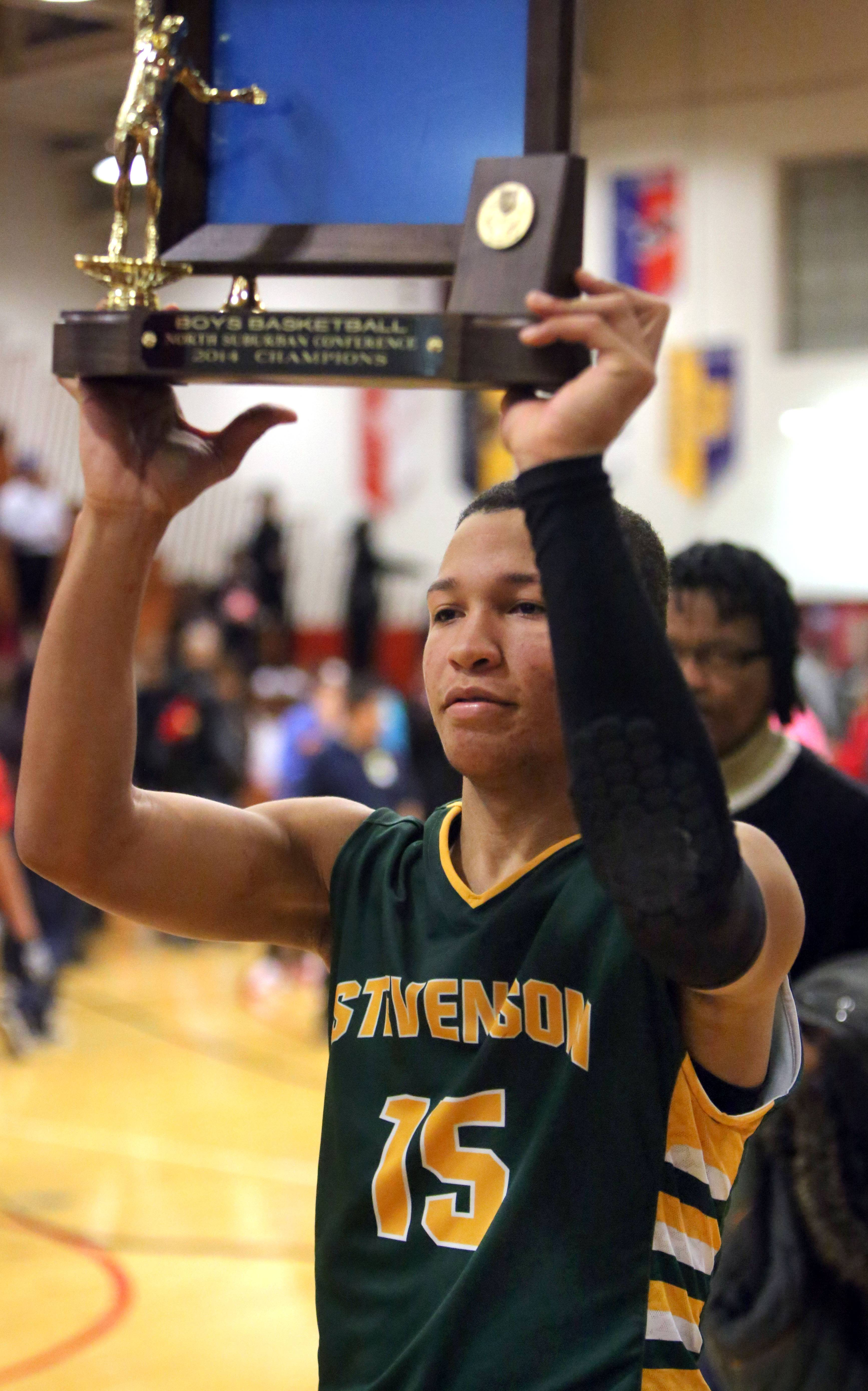 Stevenson's Jalen Brunson holds up the North Suburban Conference trophy after the Pats' victory over North Chicago in the North Suburban Conference championship game Wednesday night at North Chicago.