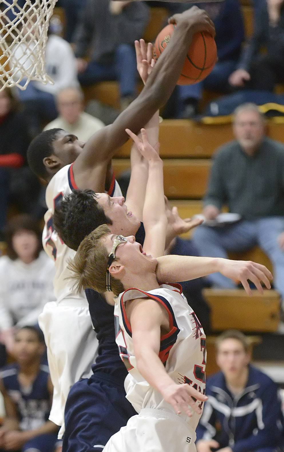 West Aurora's Roland Griffin, top, and Tommy Koth, bottom, sandwich Lake Park's Sean Moore while fighting for a rebound in the second quarter.