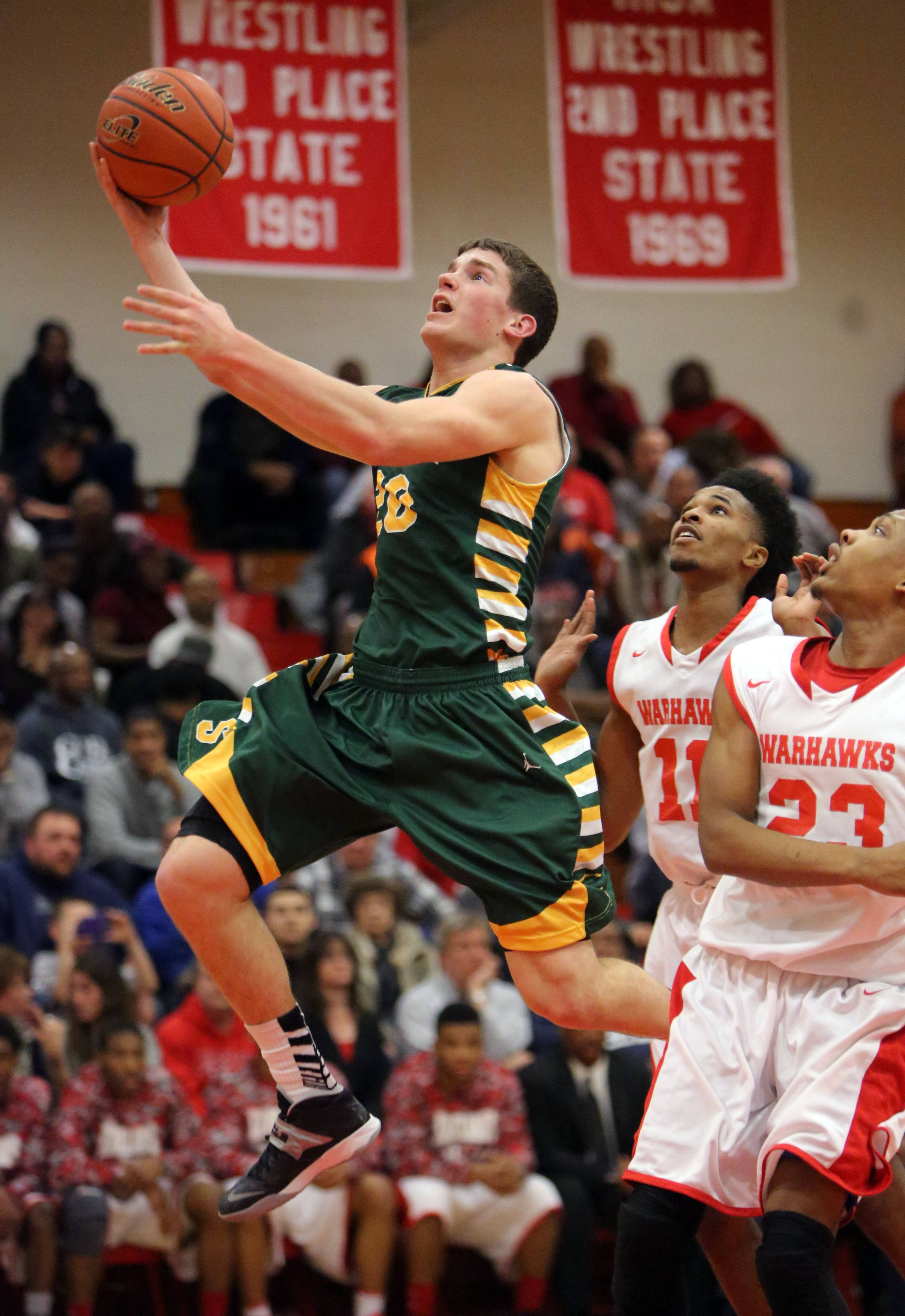 Stevenson's Matt Morrissey, left,  drives in past North Chicago's JayQuan McCloud and North Chicago's Jamero Shelton.