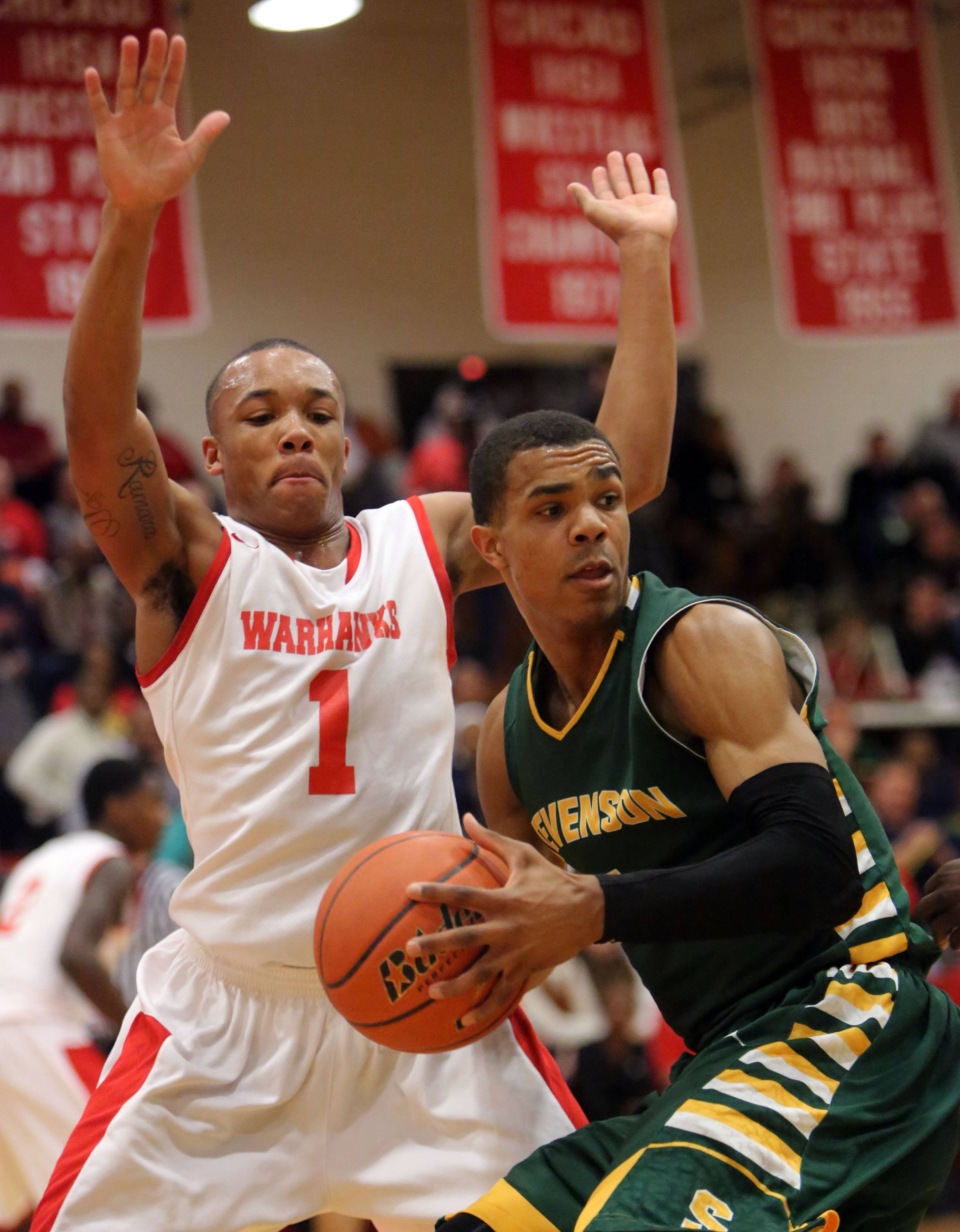 Stevenson's Connor Cashaw, right, drives in on North Chicago's Arnold Shead.