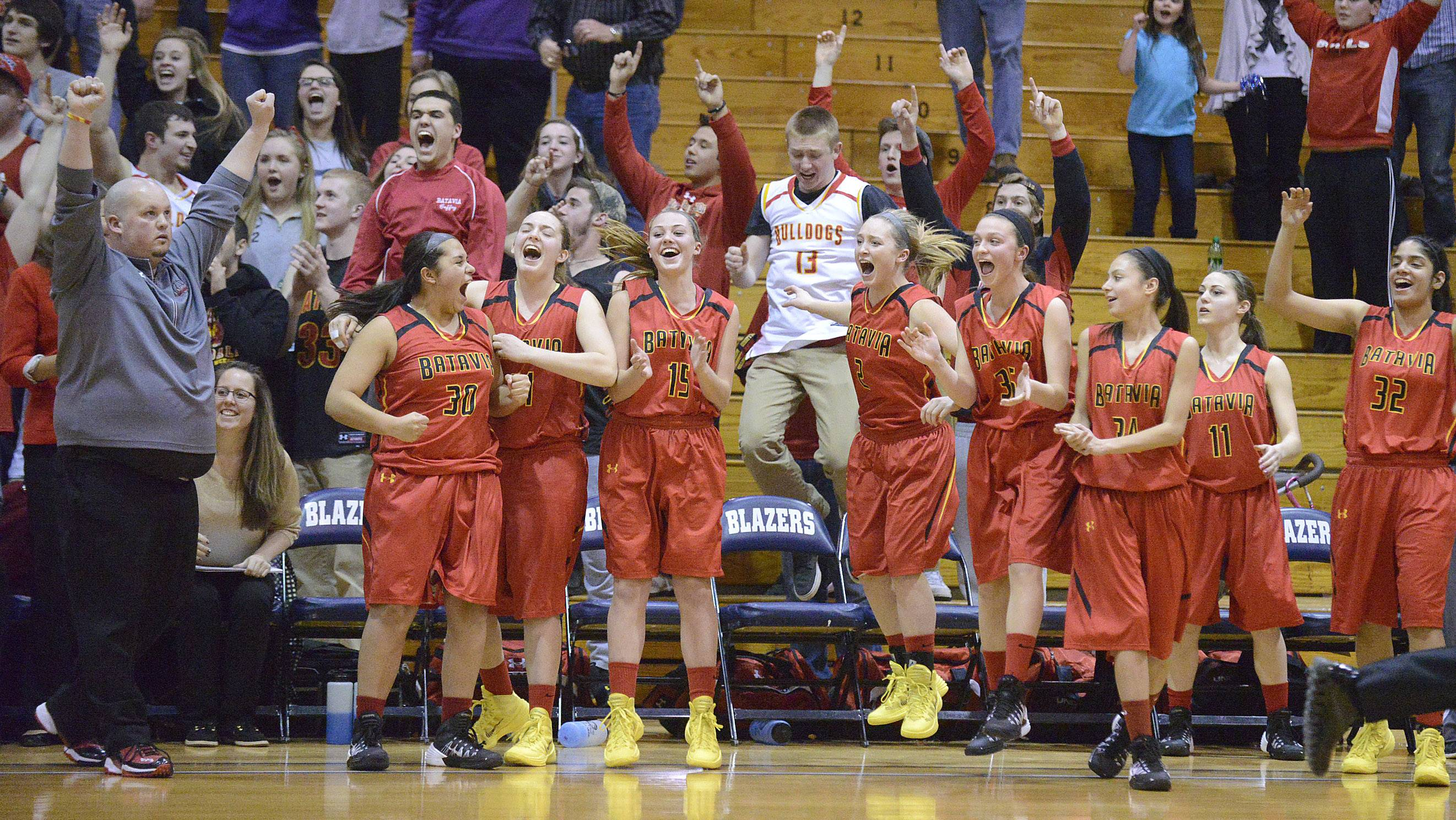 Above: Batavia coach Kevin Jensen, far left, and the Bulldogs react to beating Downers Grove North on Tuesday at Addison Trail. Below: Geneva players swarm Janie McCloughan after the junior made the winning free throw with .8 seconds left against Wheaton Warrenville South. The Bulldogs and Vikings return to Addison at 7 p.m. Thursday to play for the sectional championship.