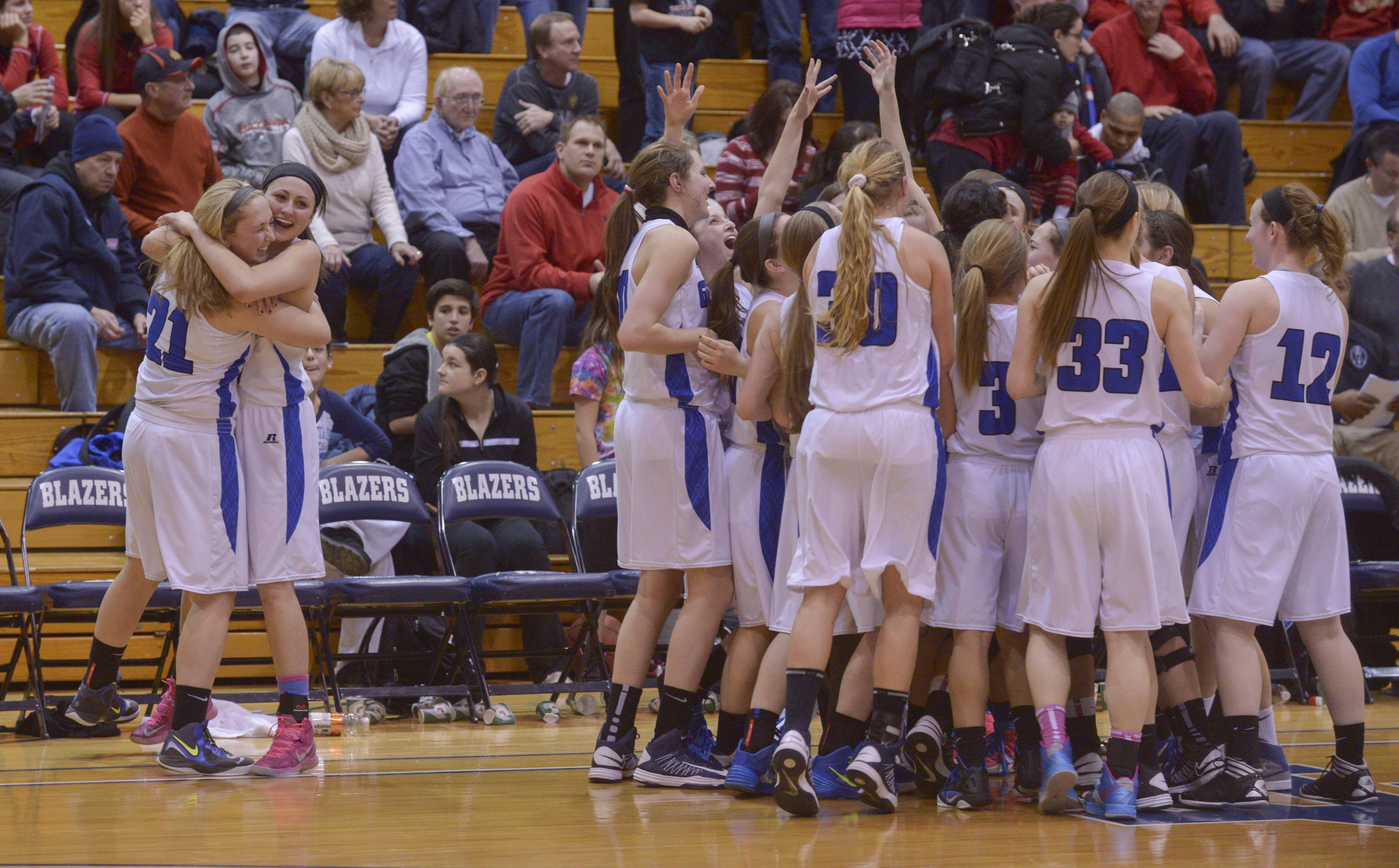 Geneva celebrates their 48-24 win over Batavia in the Class 4A girls basketball sectional final game at Addison Trail in Addison, Thursday.