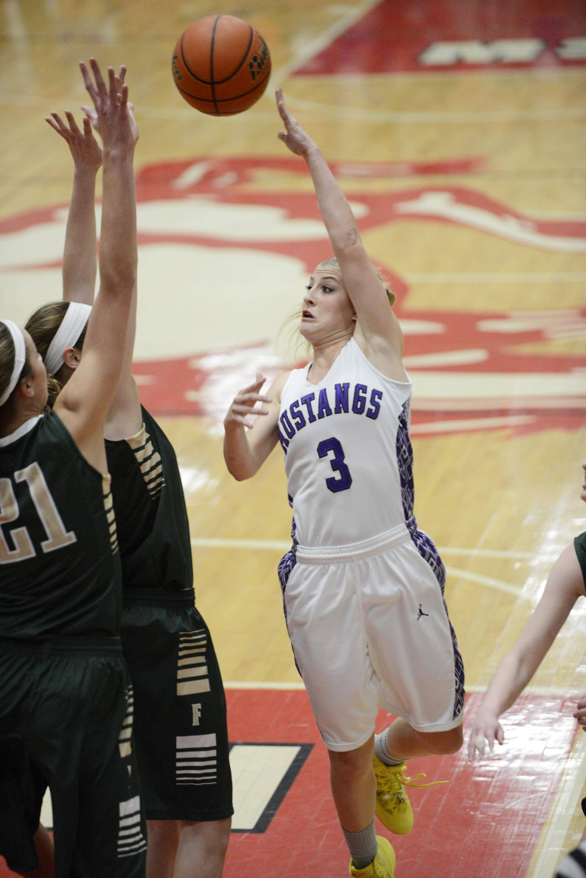 Rolling Meadows' Jackie Kemph delivers a pass over Fremd defenders Thursday in the Barrington Class 4A sectional championship game.