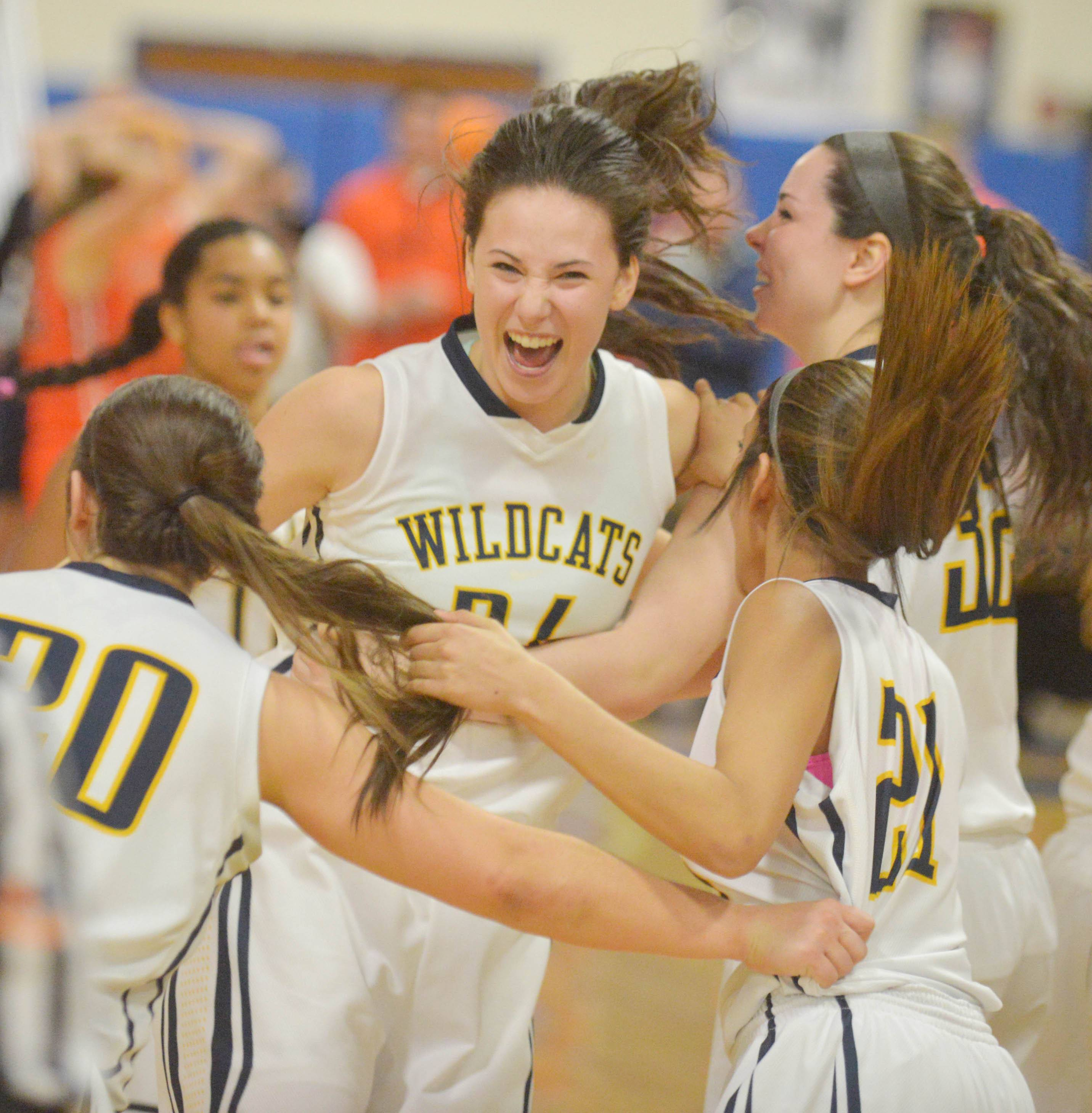 (24) Bryce Menendez of Neuqua can't hold back the smiles after the big win during the Neuqua Valley vs. Oswego Class 4A Joliet Central girls basketball sectional final Thursday.  She was bing hugged by (20) Niki Lazar (21) Kiran Rehal and (32) Gwen Berglind.