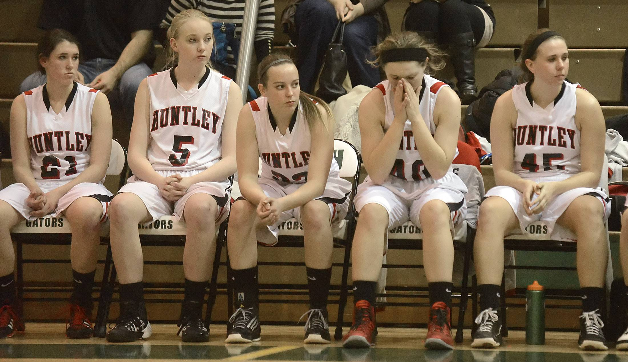 Huntley's Samantha Andrews wipes away tears while sitting between teammates Kelli Rubino, left, and Rachel Zobott after the Red Raiders' loss to Rockford Boylan in the Class 4A sectional championship at Crystal Lake South High School Thursday.
