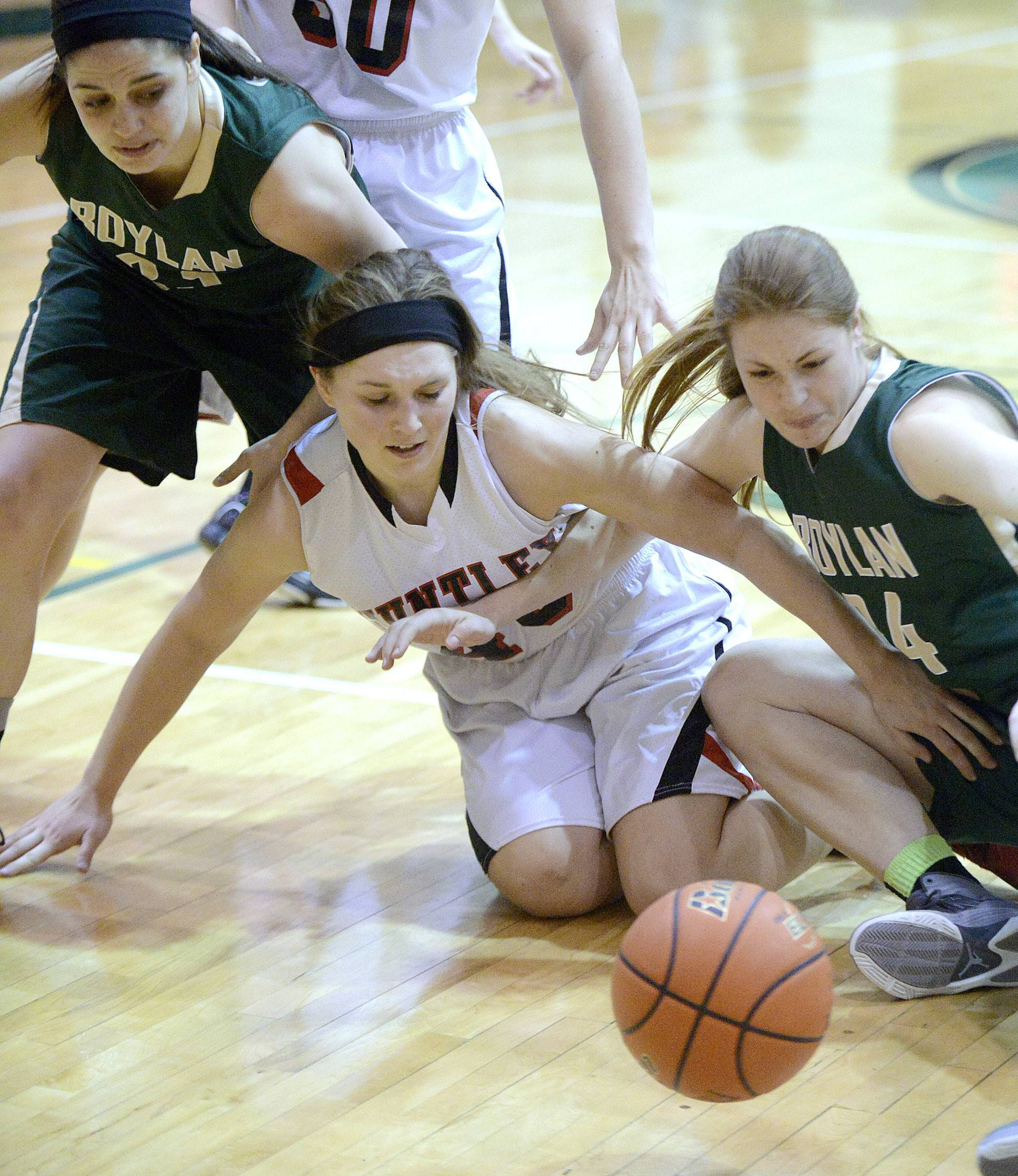 Huntley's Ali Andrews, center, tumbles to the floor with Rockford Boylan's Amanda Black, left, and Halle Stull, right, in the second quarter of the Class 4A sectional championship at Crystal Lake South Thursday.