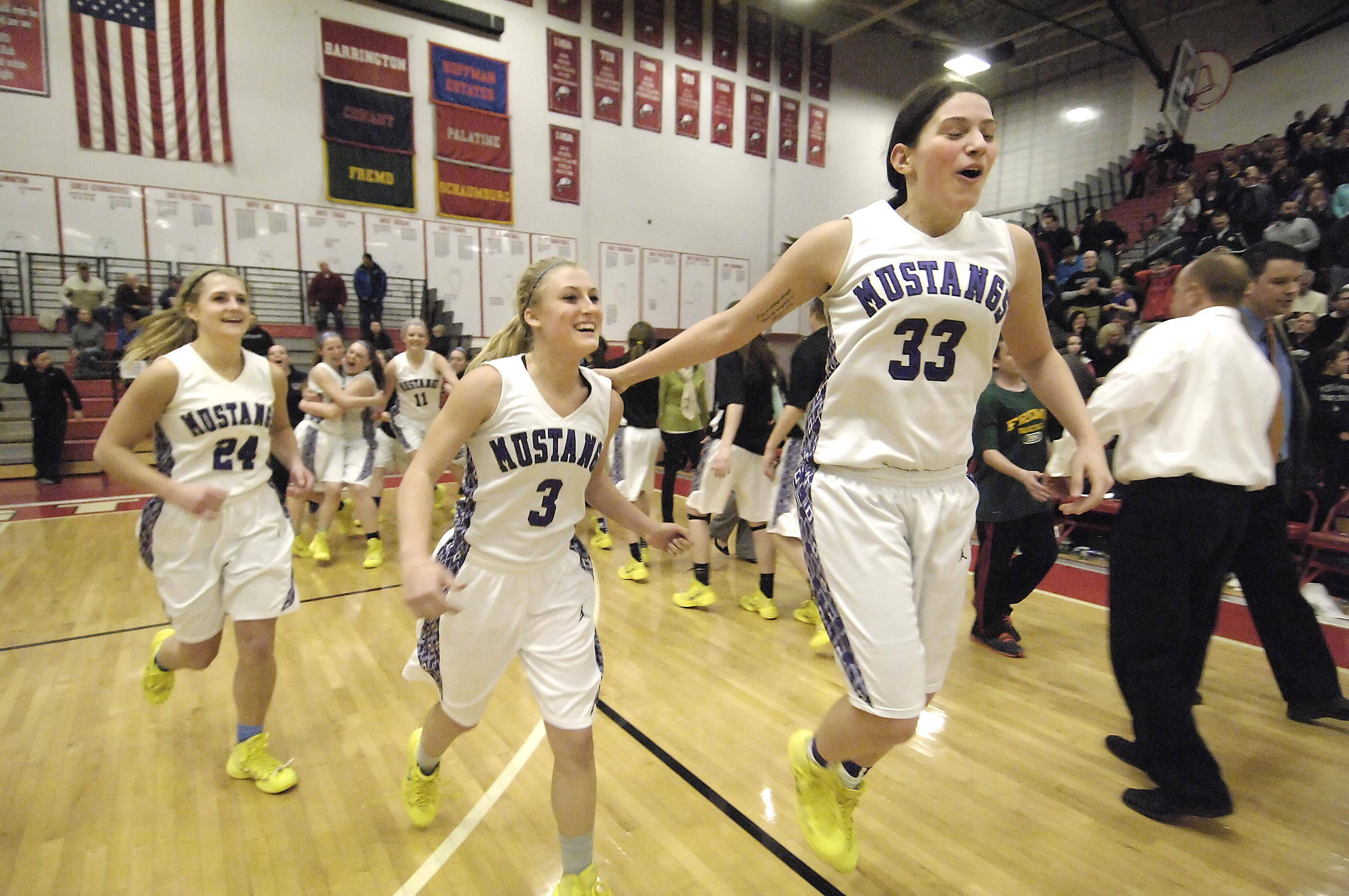 Rolling Meadows' Ashley Montanez, right, Jackie Kemph, and Alexis Glasgow, left, celebrate their win over Fremd .