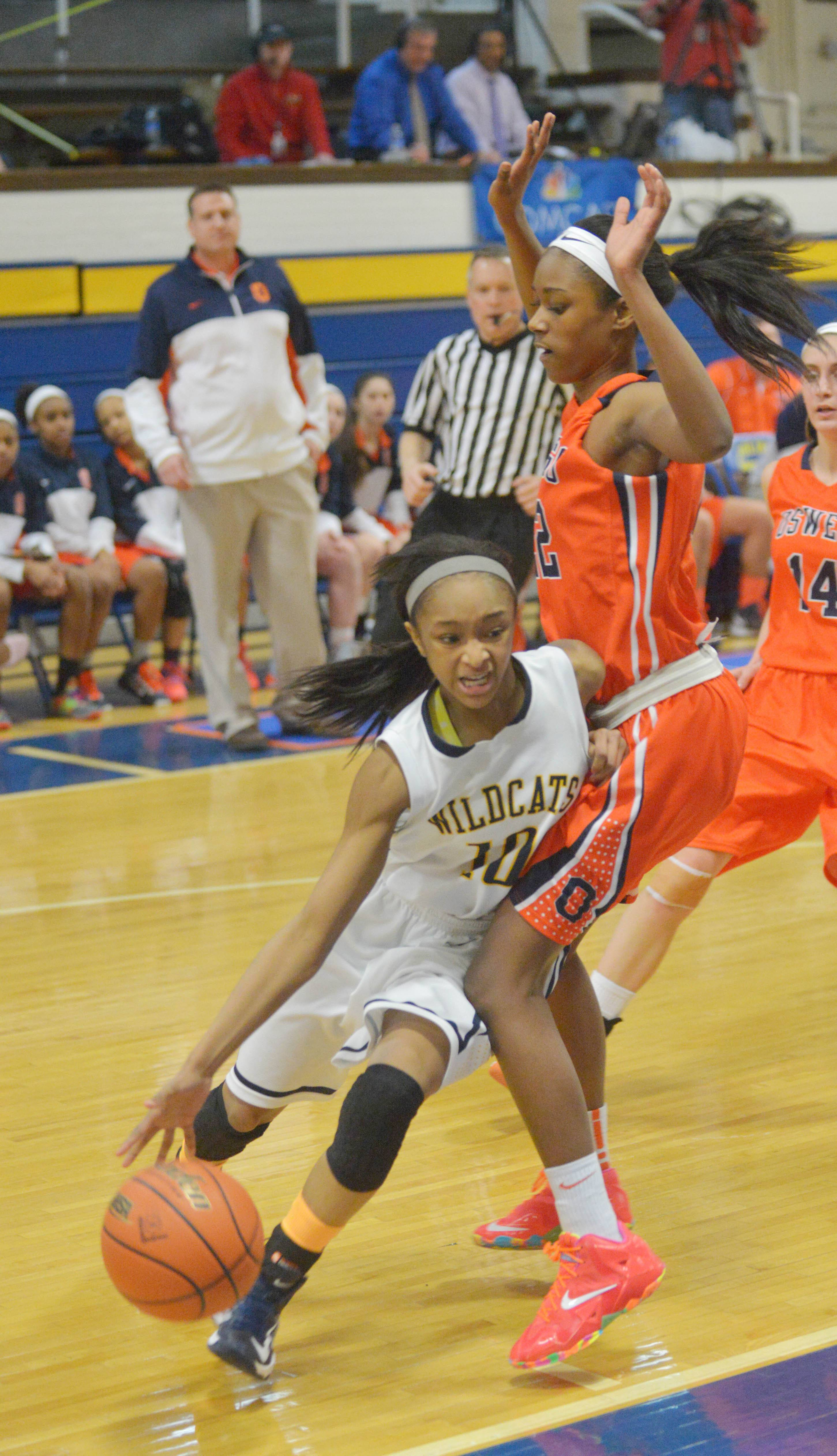 Myia Starks of Neuqua Valley drives the ball around Amri Wilder of Oswego.