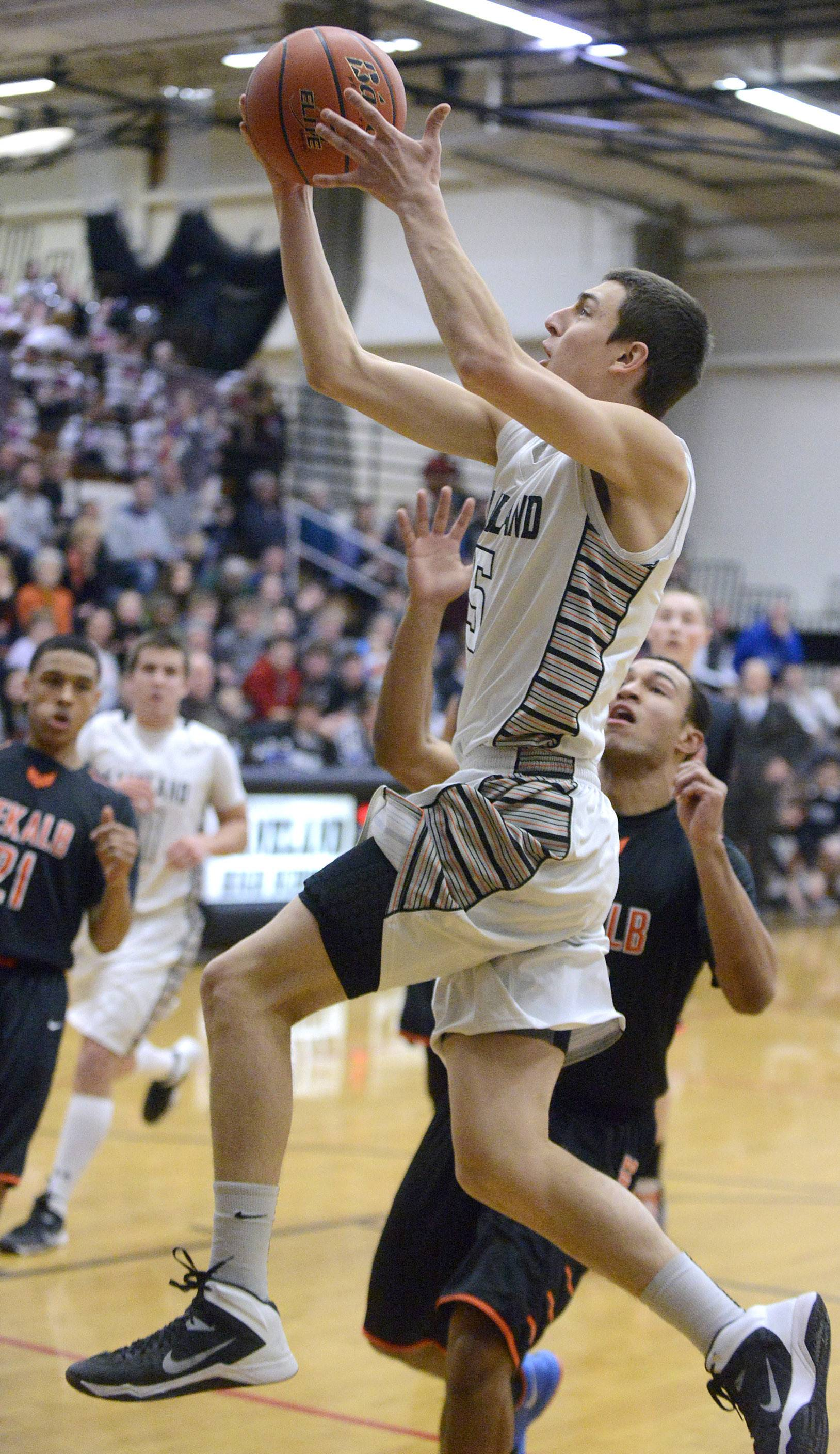 Kaneland's John Pruett drives by DeKalb's Dre Brown Friday.