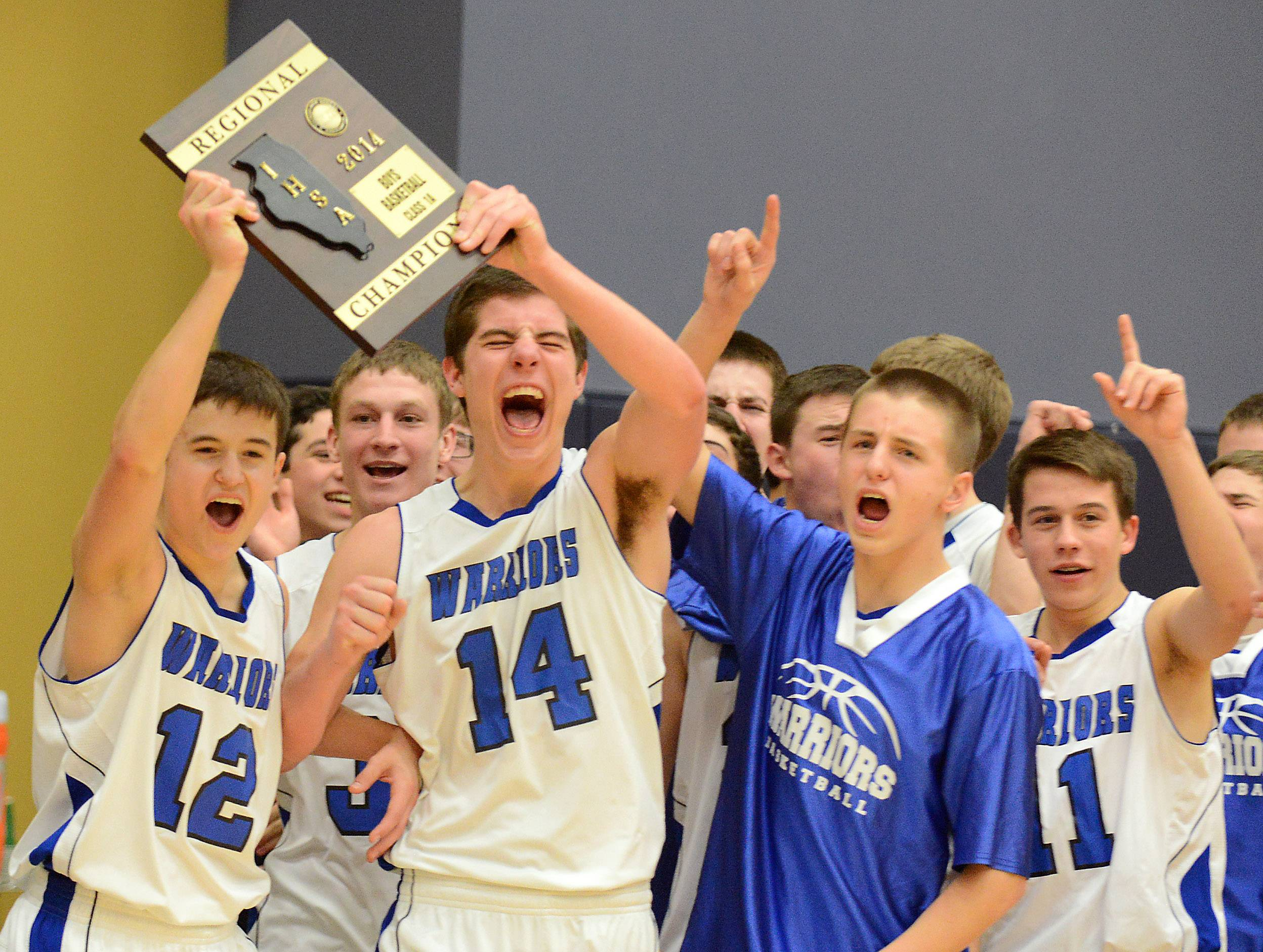 Westminster Christian's Dillion Rejman (12) and Sam Carani (14) hoist the championship plaque following their win over Harvest Christian during Friday's regional championship game at Harvest Christian Academy in Elgin.
