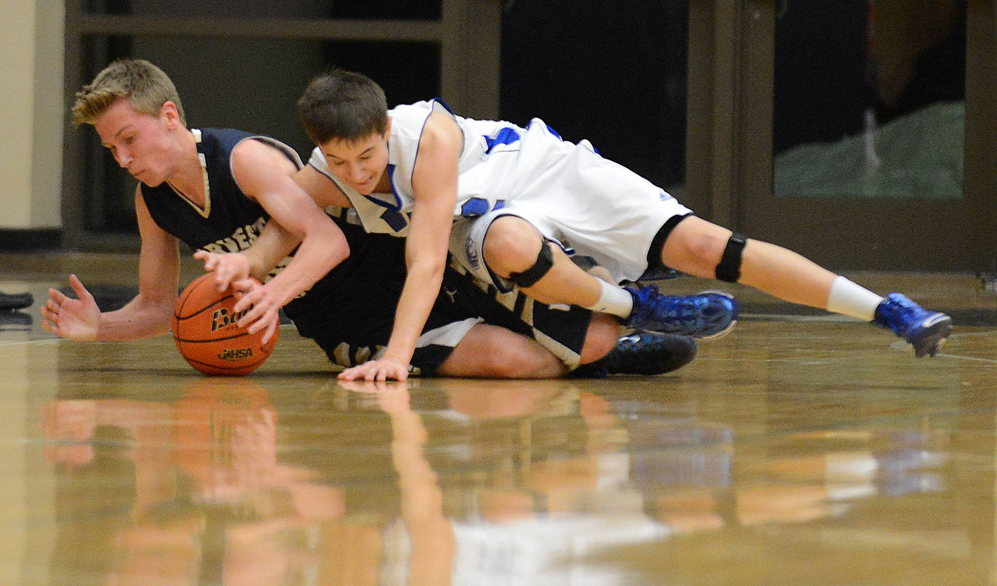 Harvest Christian's Jake Adams (10), left, and Westminster Christian's Dillion Rejman (12) battle for a loose ball during Friday's regional championship game at Harvest Christian Academy in Elgin.