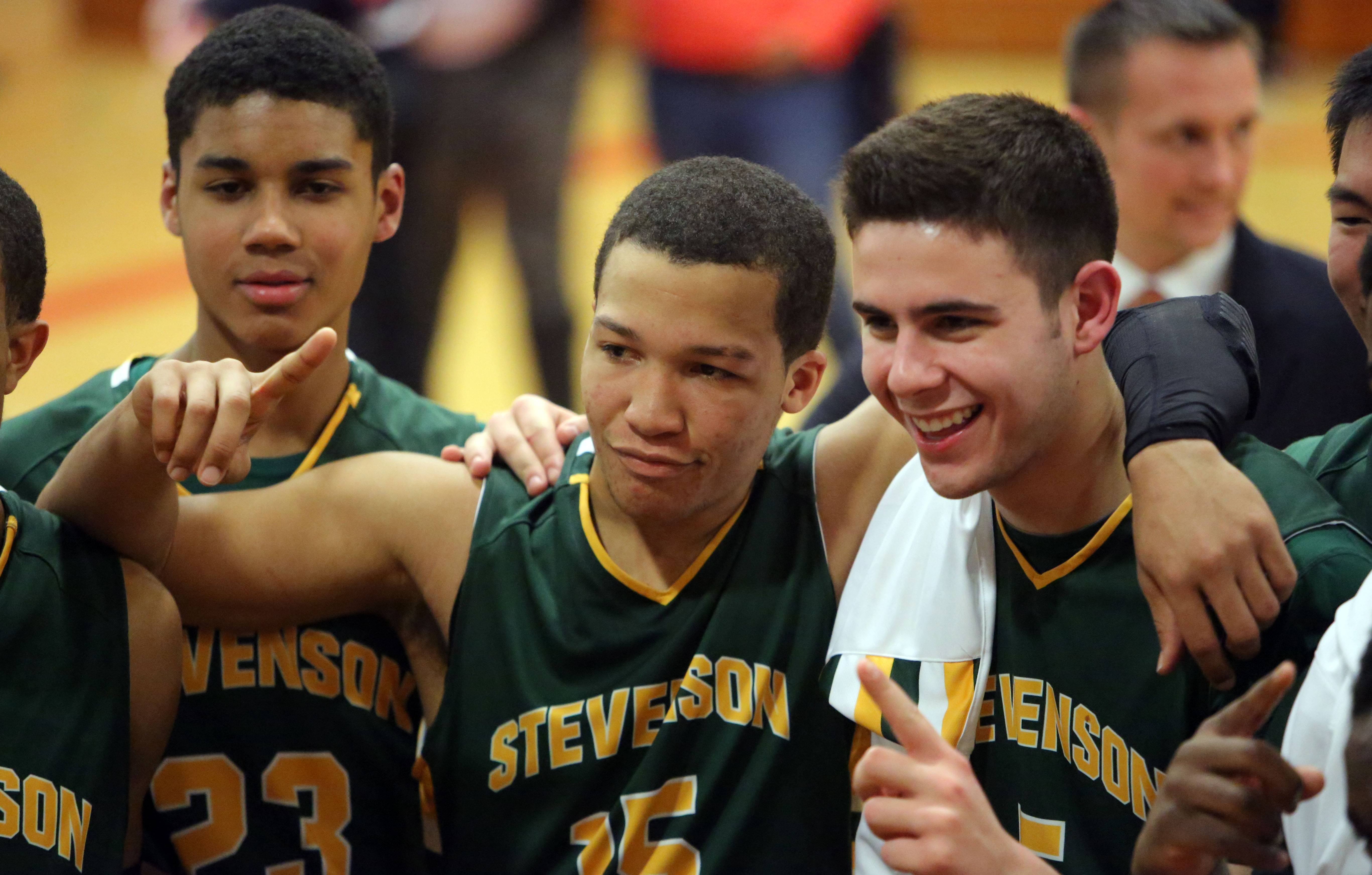 Stevenson's Jalen Brunson, left, and Parker Nichols give the number one sign as they pose for pictures after their blowout win over North Chicago in the North Suburban Conference championship game Wednesday night at North Chicago High School.
