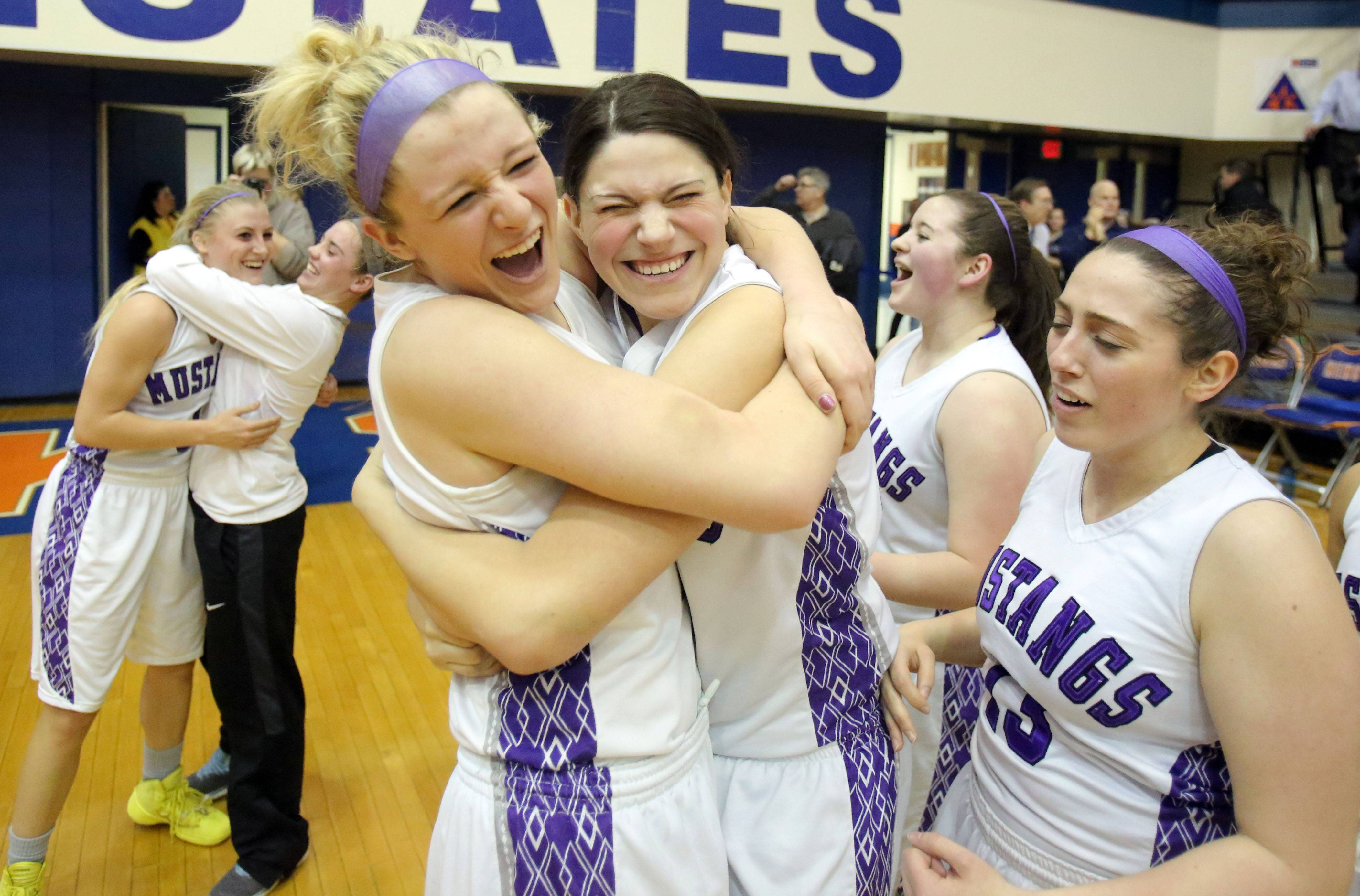 Rolling Meadows' Jenny Vliet, foreground left, embraces teammate Ashley Montanez, after the Mustangs beat New Trier 60-43 in the Class 4A supersectional at Hoffman Estates on Monday.