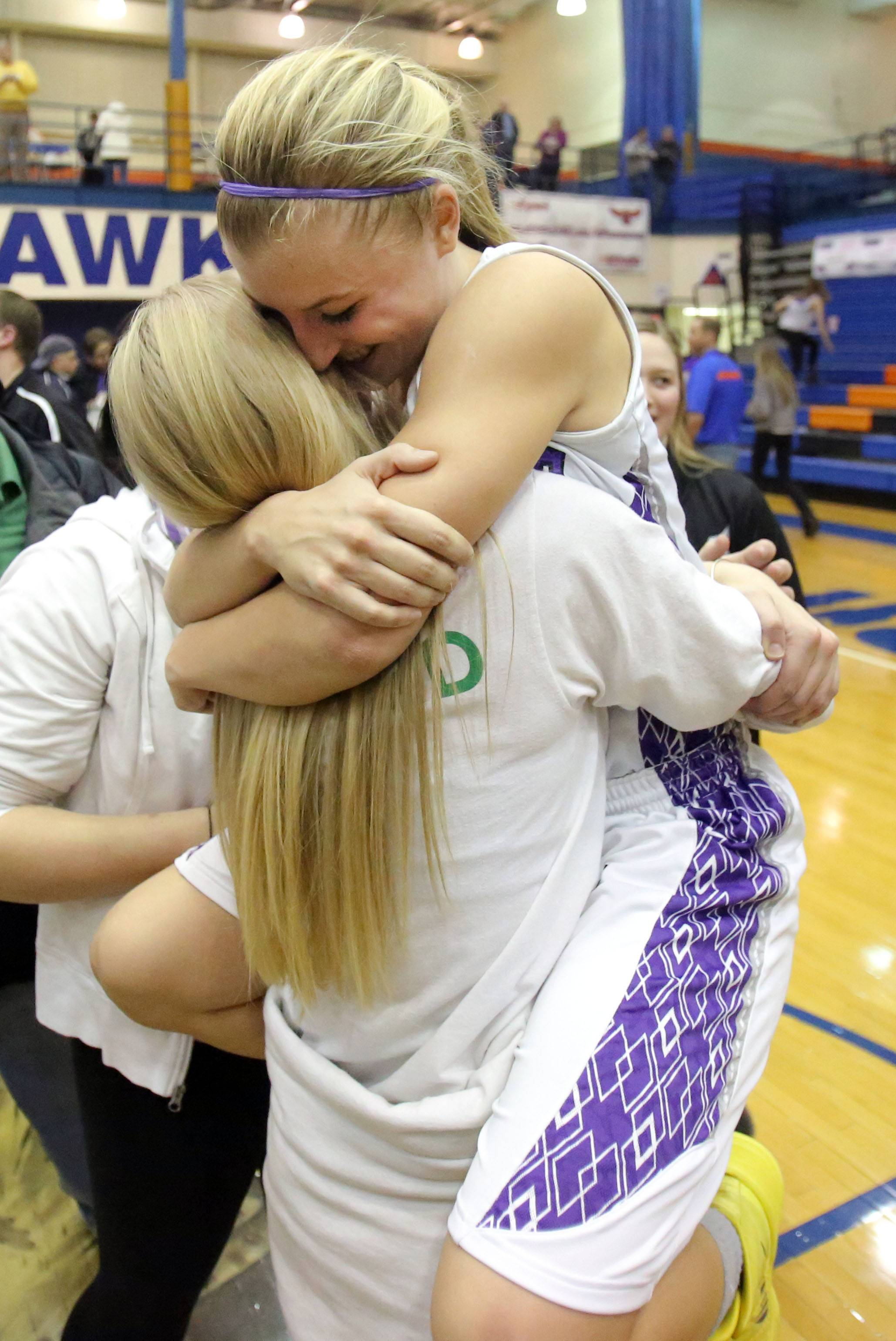 Rolling Meadows' Jackie Kemph, right, jumps into the arms of friend Allie Skowron after the Mustangs beat New Trier 60-43 in the Class 4A supersectional at Hoffman Estates on Monday.