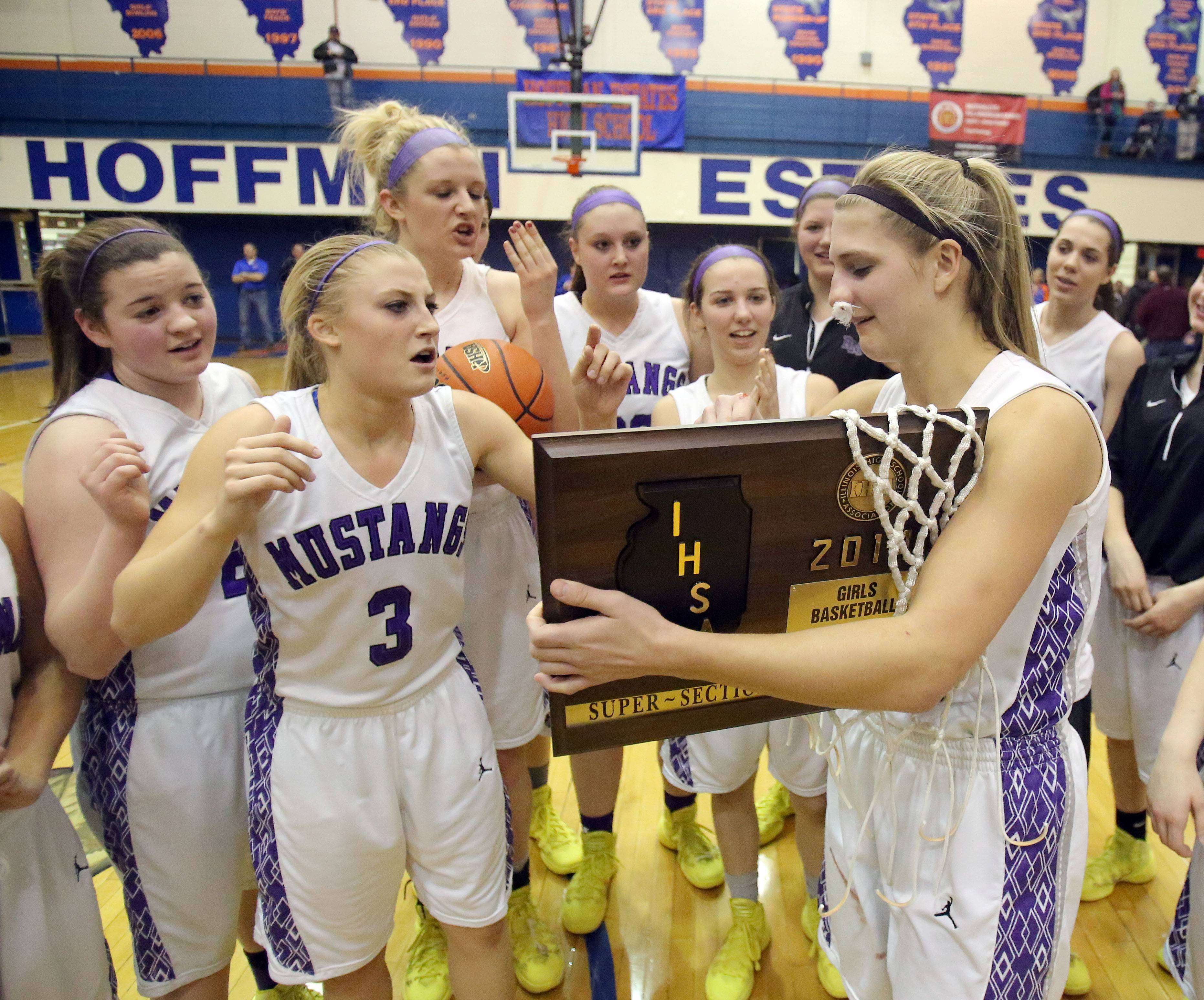 Rolling Meadows players gather around Alexis Glasgow as she receives the supersectional trophy following the Mustangs' 60-43 victory over New Trier in Class 4A supersectional play at Hoffman Estates on Monday.