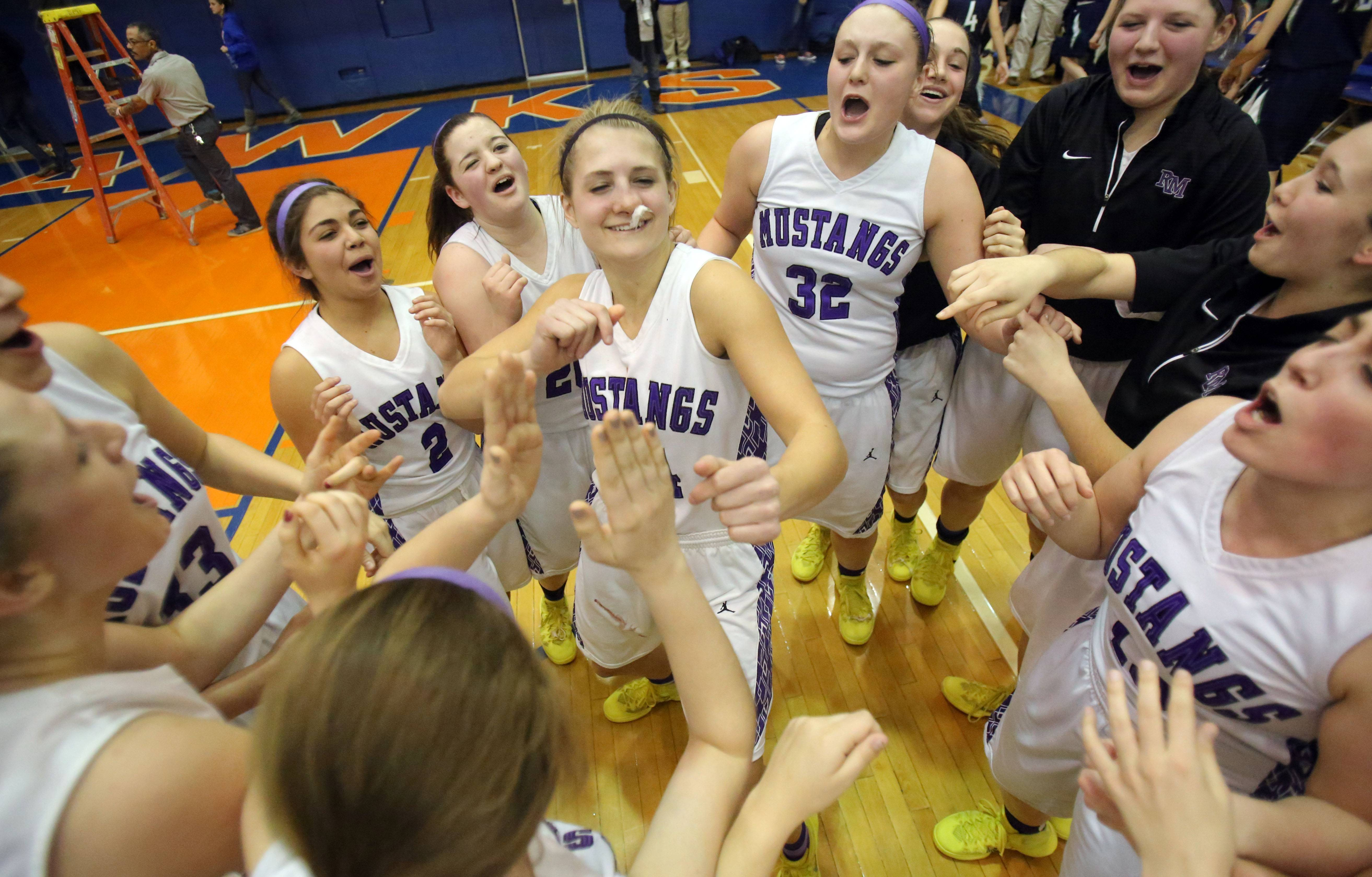 Rolling Meadows' Alexis Glasgow doesn't let a suspected broken nose prevent her from joining a victory dance following the Mustangs' 60-43 victory over New Trier in Class 4A supersectional play at Hoffman Estates on Monday.