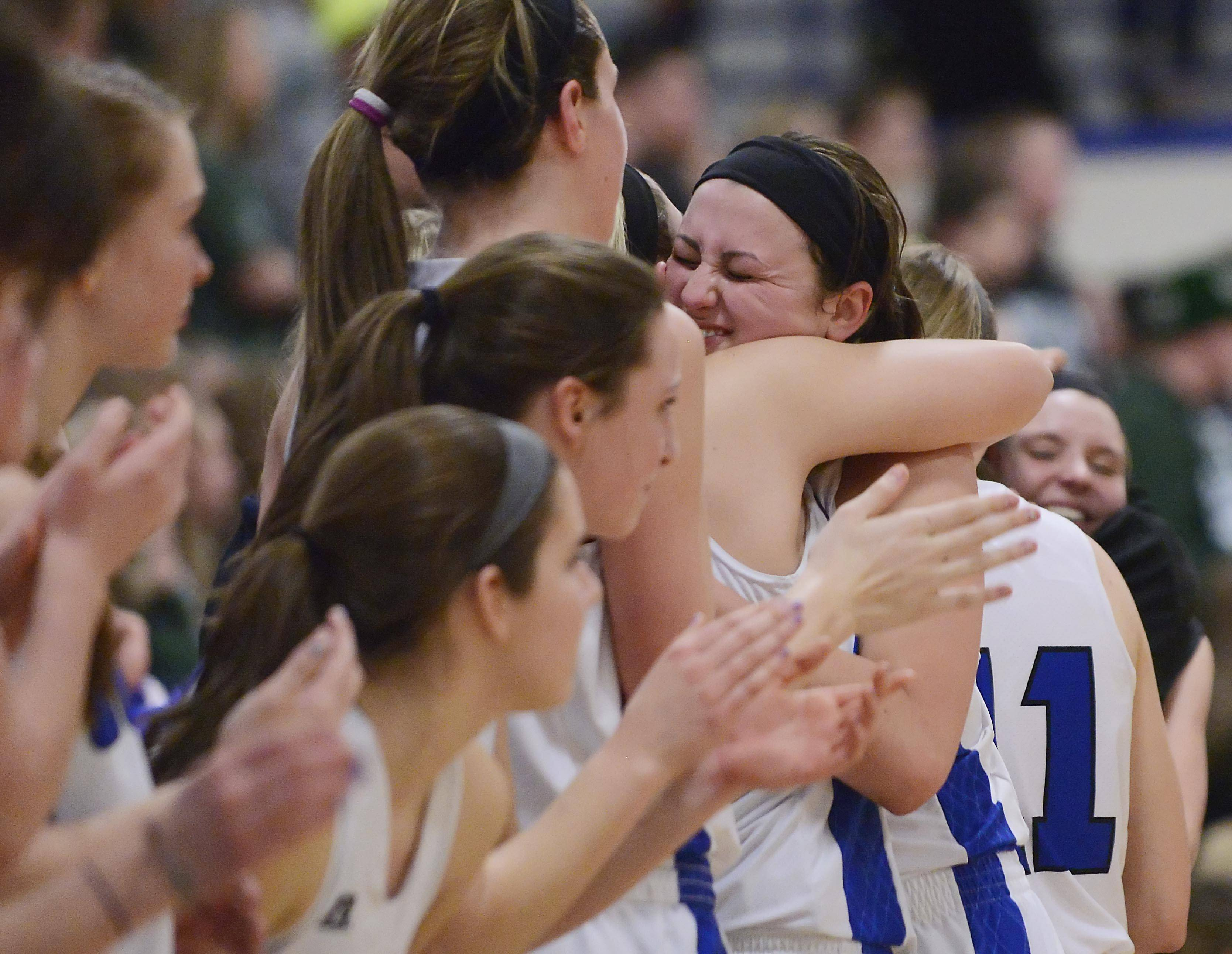Geneva's Abby Novak is hugged by teammates as she come out of the game with seconds left as the Vikings defeat Rockford Boylan Monday in the 4A supersectional championship game at Judson University in Elgin.