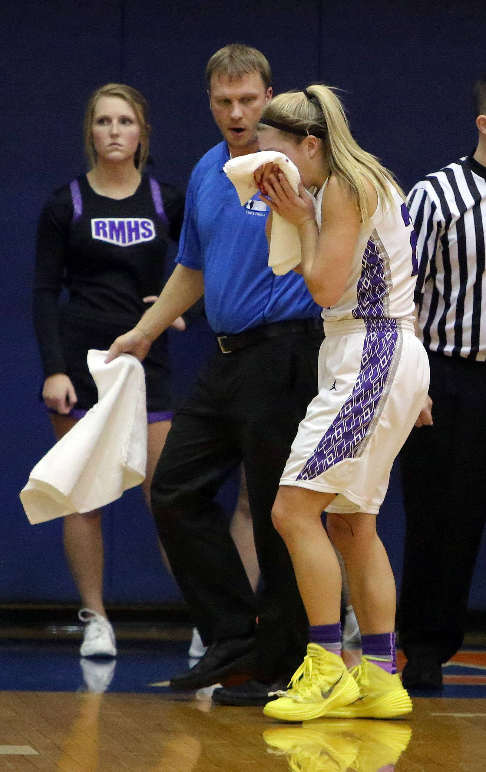 Rolling Meadows' Alexis Glasgow is taken off the court after getting elbowed in the nose.
