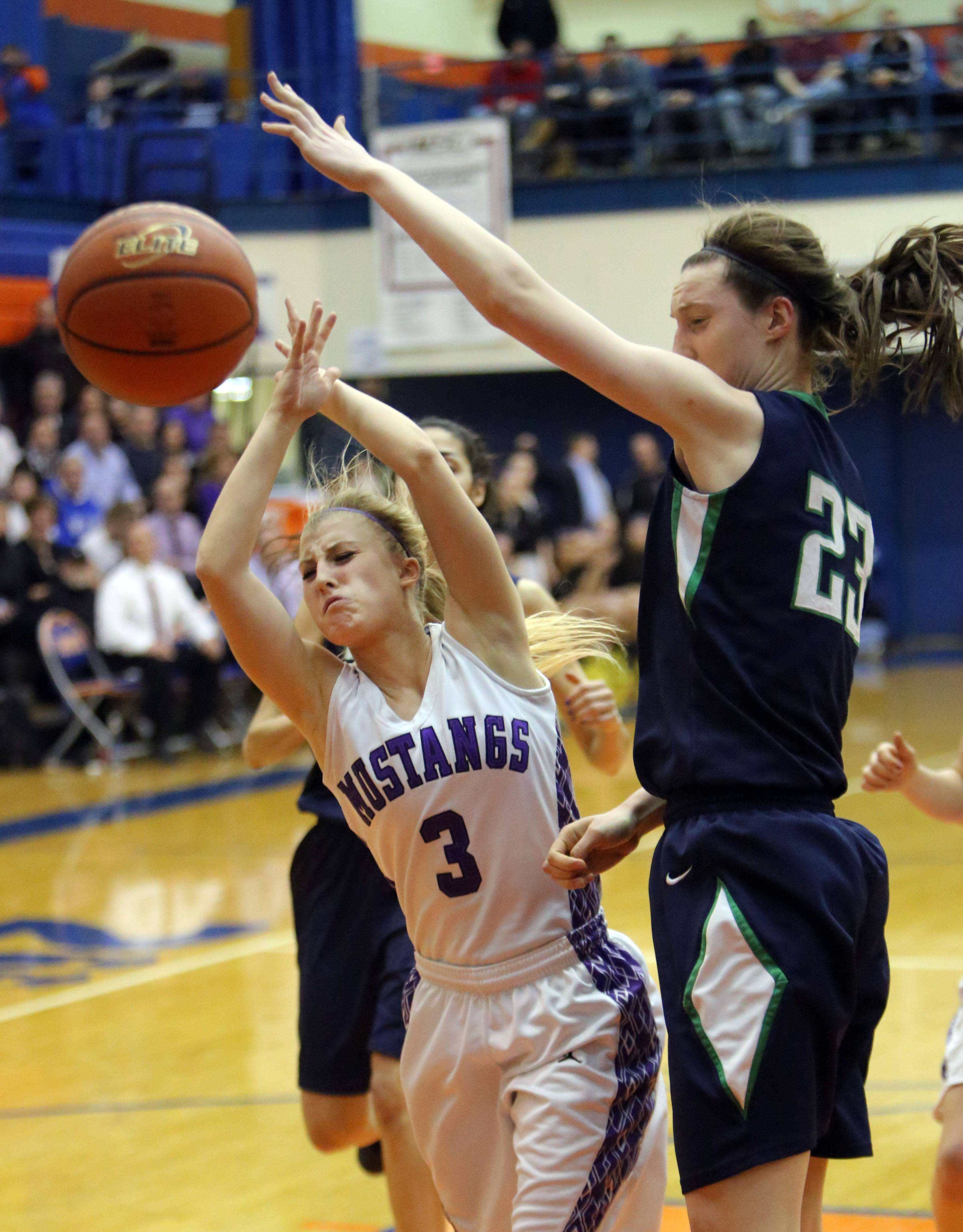 Rolling Meadows' Jackie Kemph, left, gets fouled by New Trier's Jeannie Boehm.