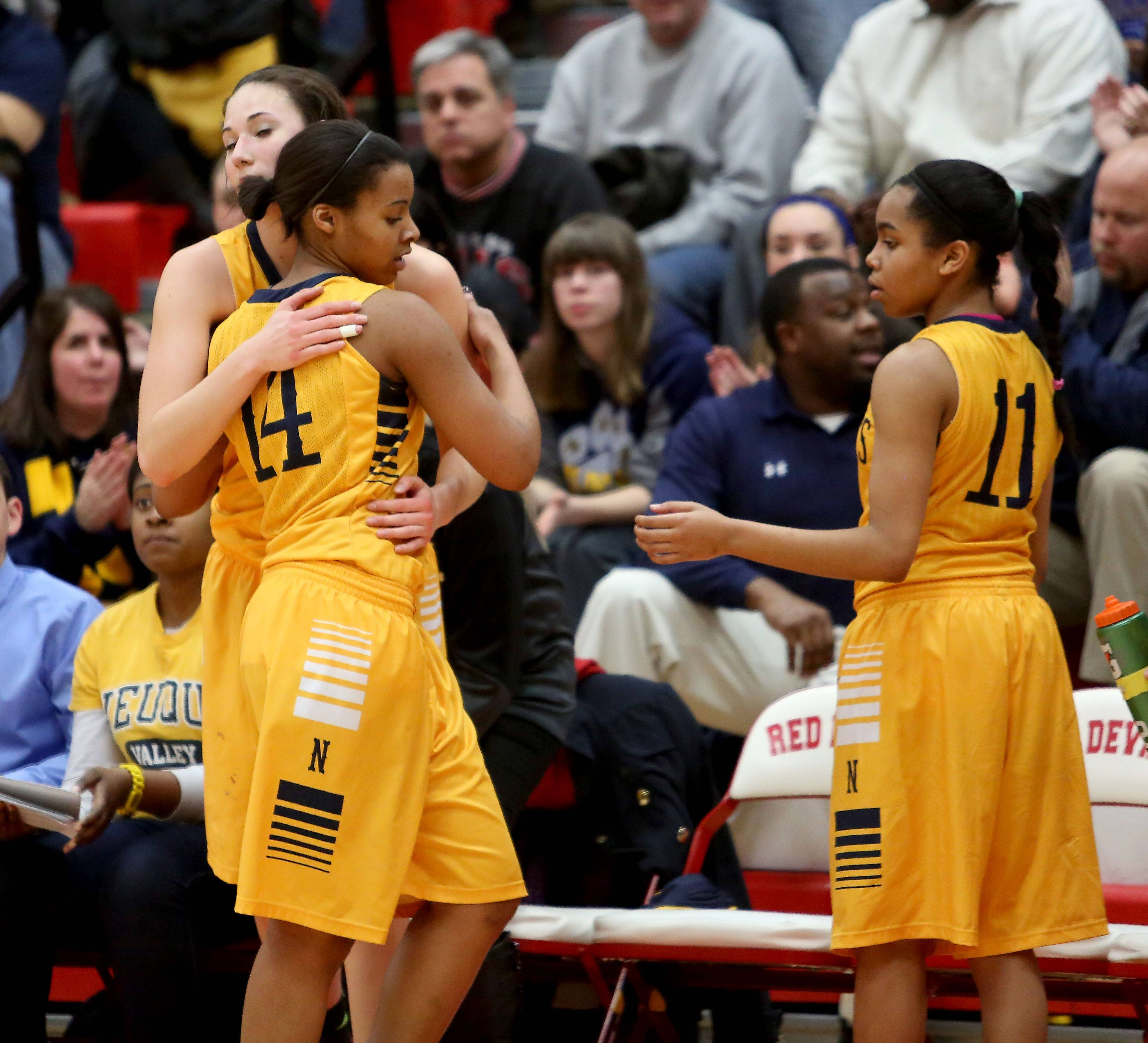 Neuqua Valley's Najee Smith, left, gets a hug from teammates as she comes off the floor.