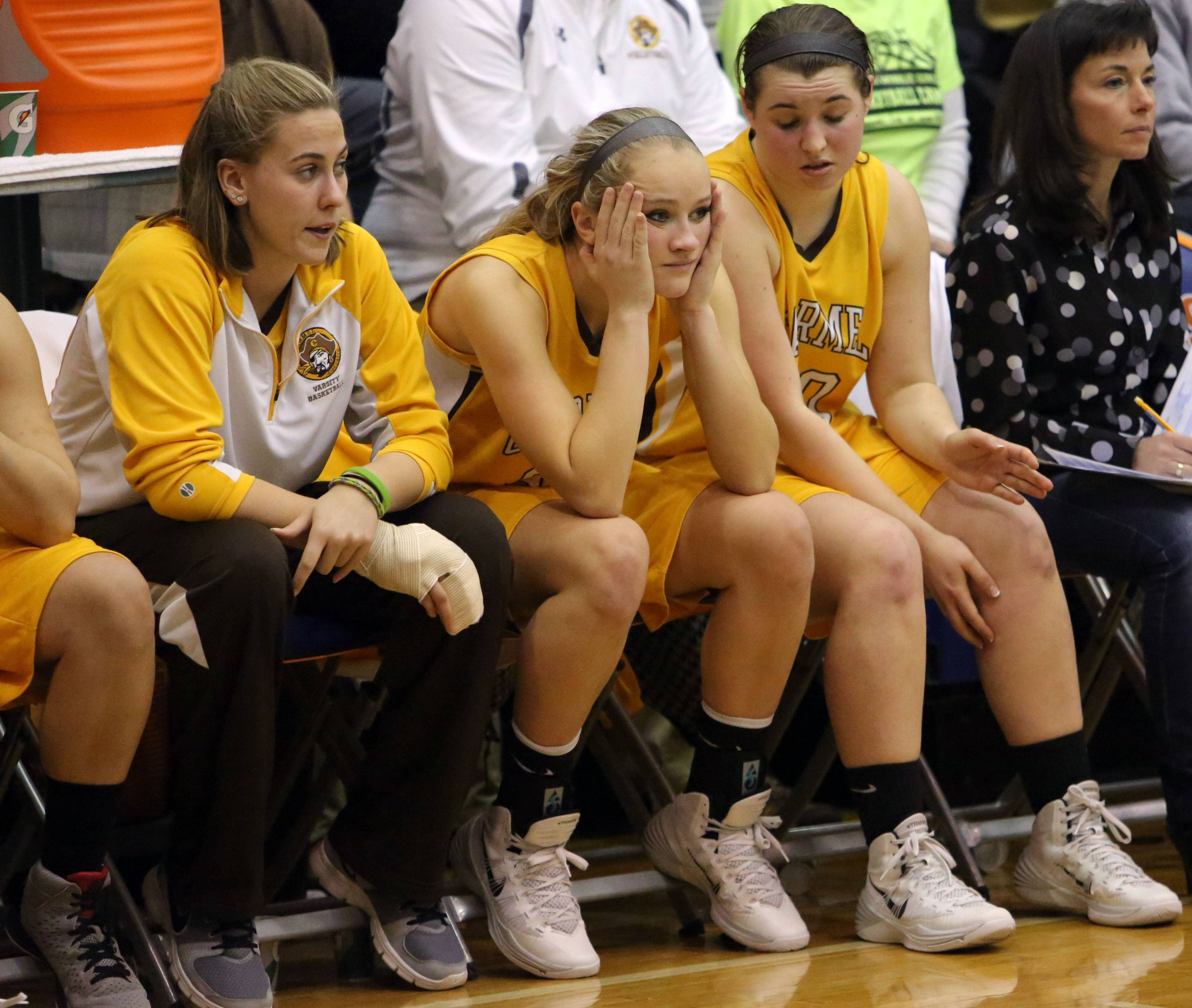 Players on Carmel's  bench sit in disbelief during their loss.