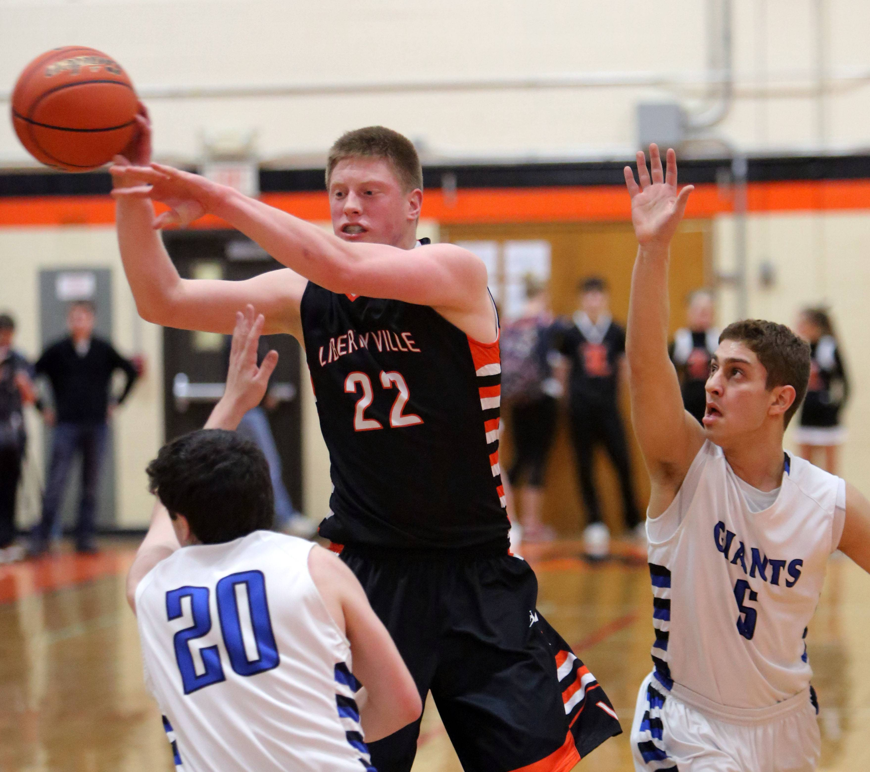 Libertyville's Jack Lipp (22) passes around Highland Park's Jacon Iden, left, and Max Goshen during Class 4A regional semifinal play at Libertyville on Tuesday.