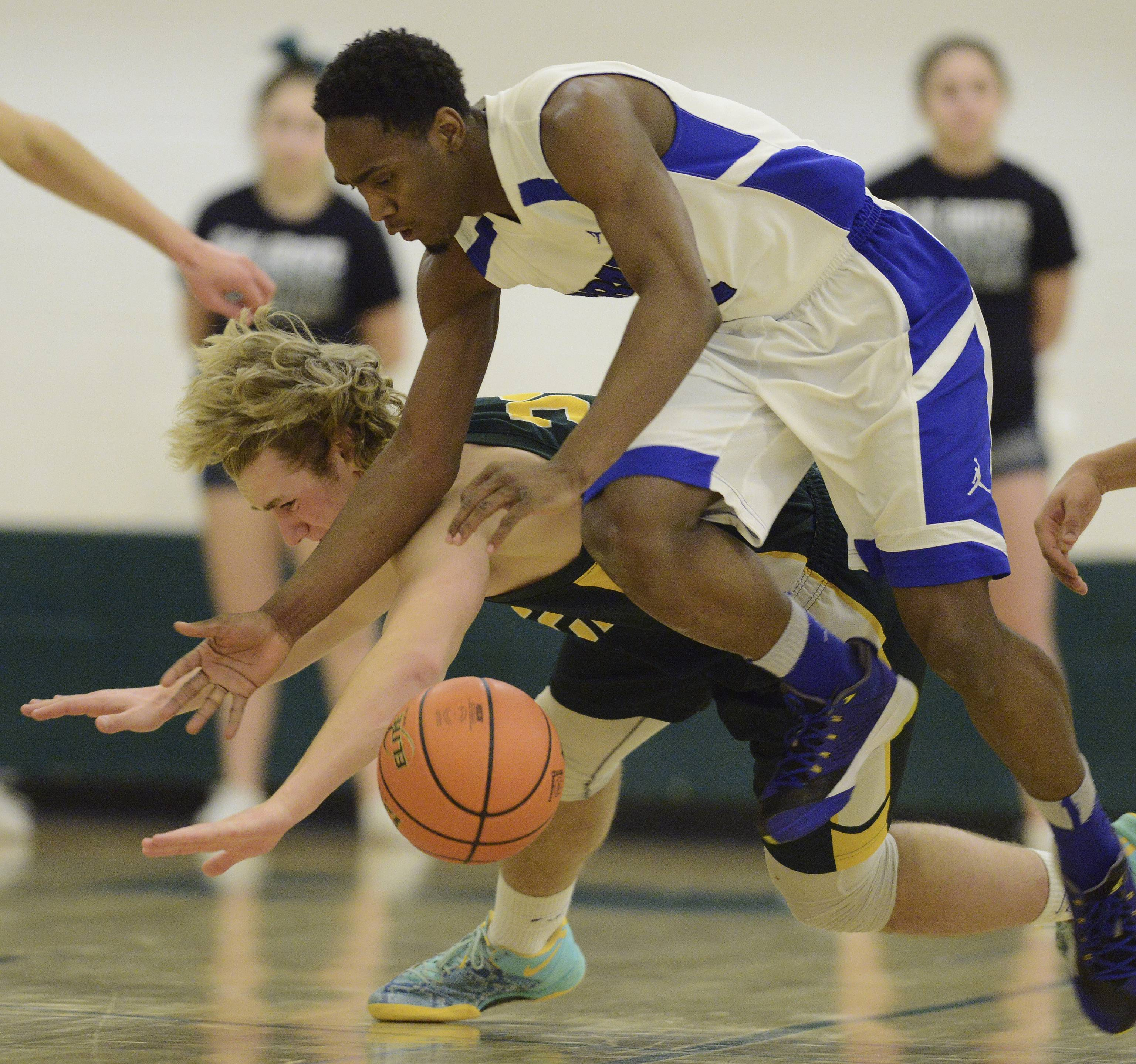 Elk Grove's Adam O'Malley, left, and Proviso East's Alano Span make contact while trying to control a loose ball .